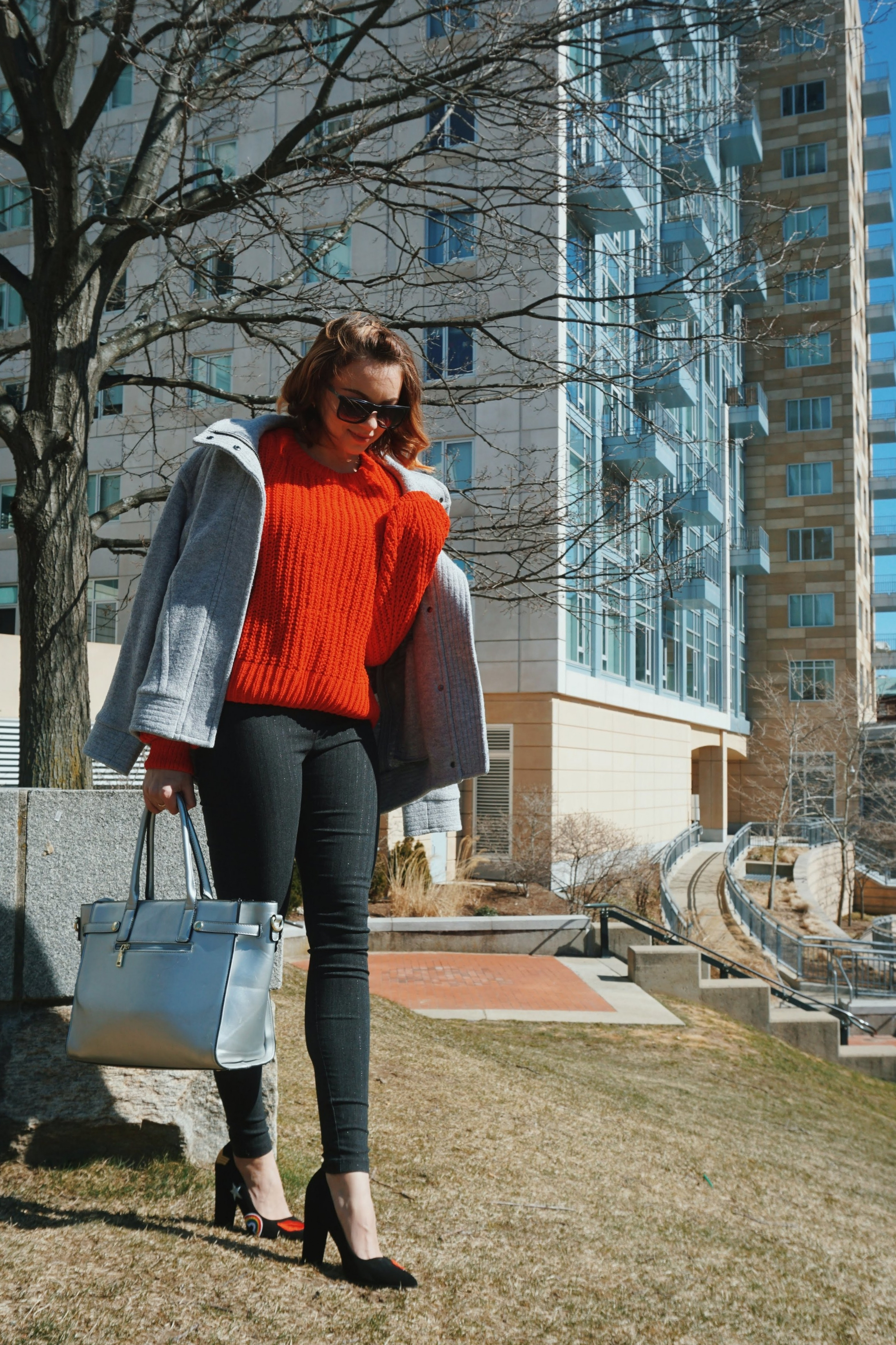 Lifestyle blogger posing on a grass, wearing a chic outfit: skinny gray pants, red sweater, gray jacket, black heels with rainbows, and silver bag.