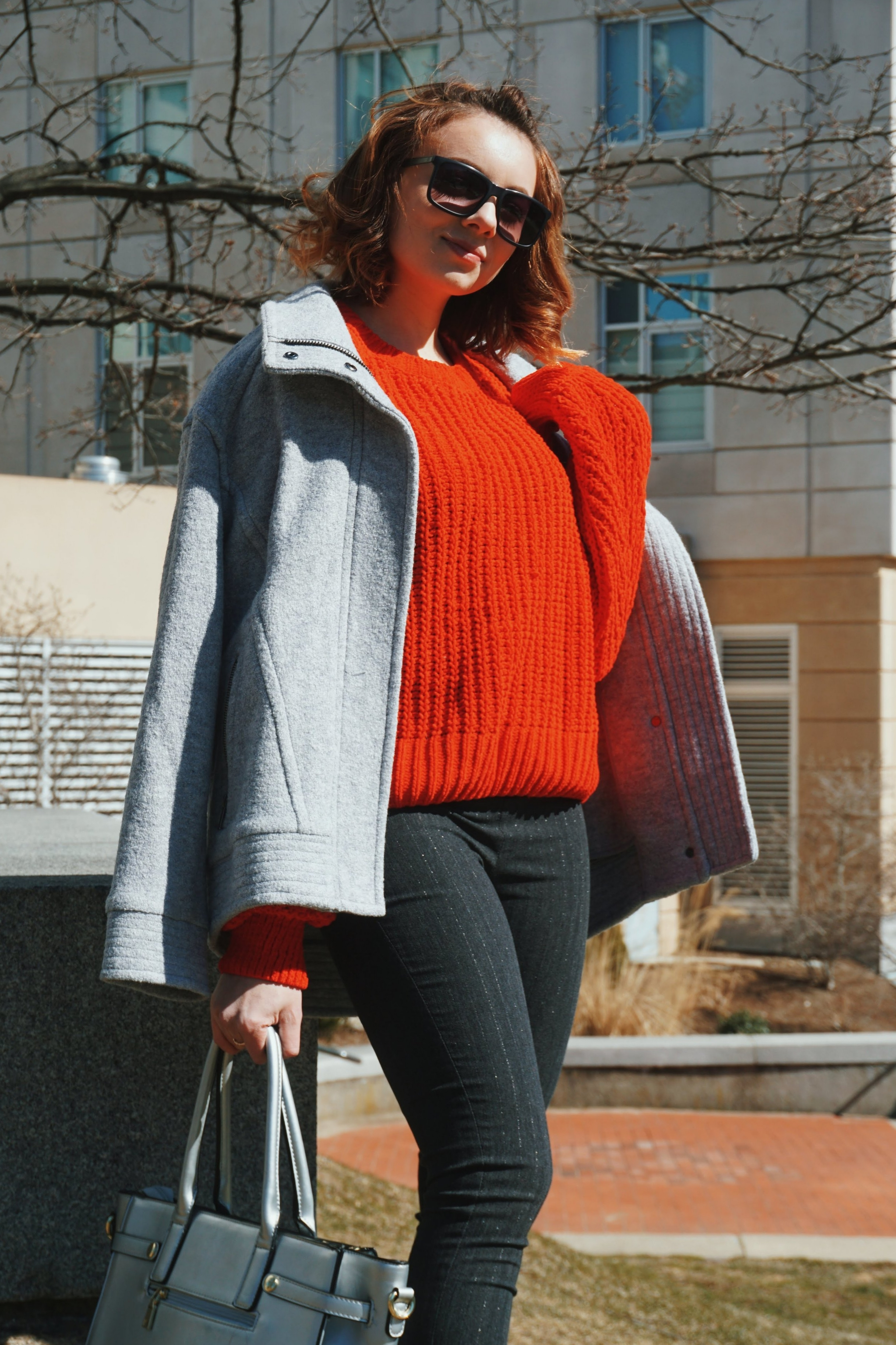 A close-up of an outfit: red loose sweater, gray baggy coat, dark gray skinny pants, silver purse, big black sunglasses.