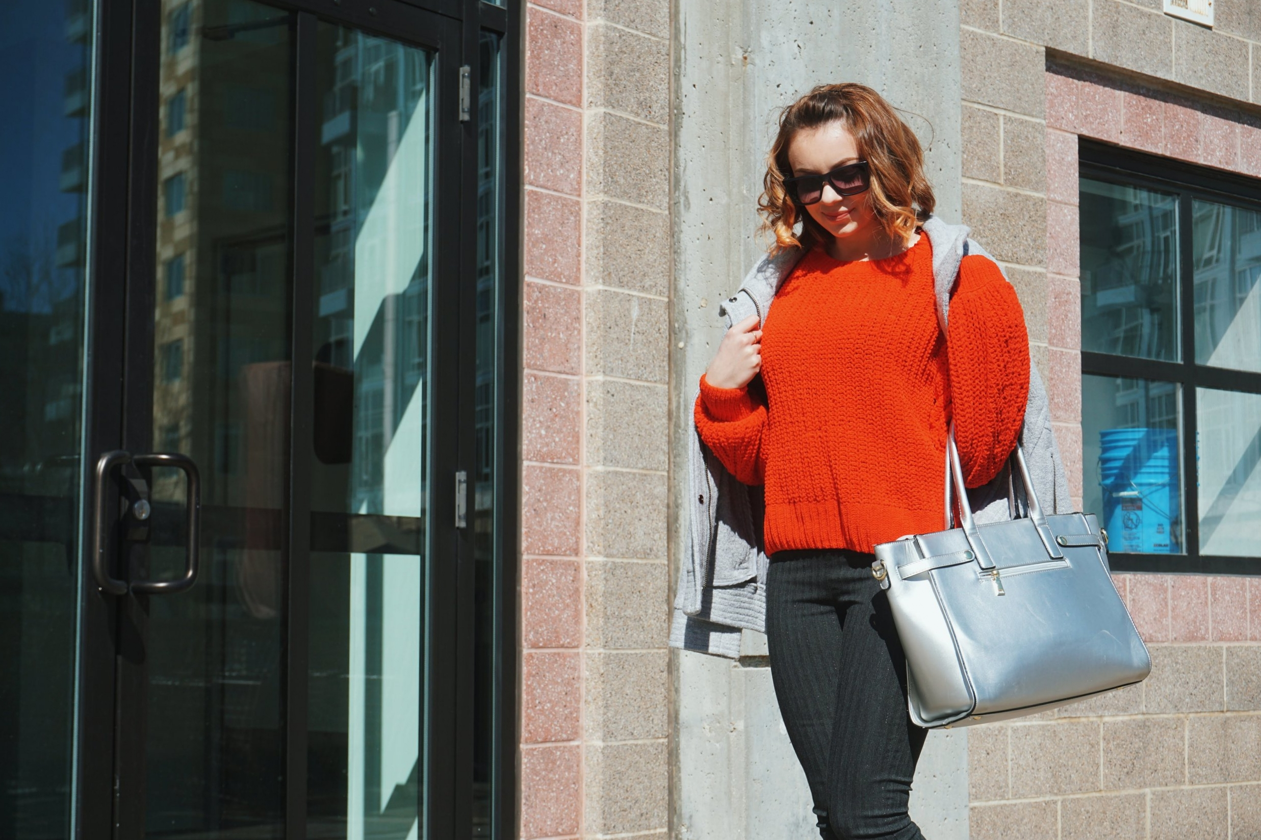 A girl wearing a comfy and chunky red sweater, gray jacket on top of the sweater, dark gray skinny pants, silver bag.