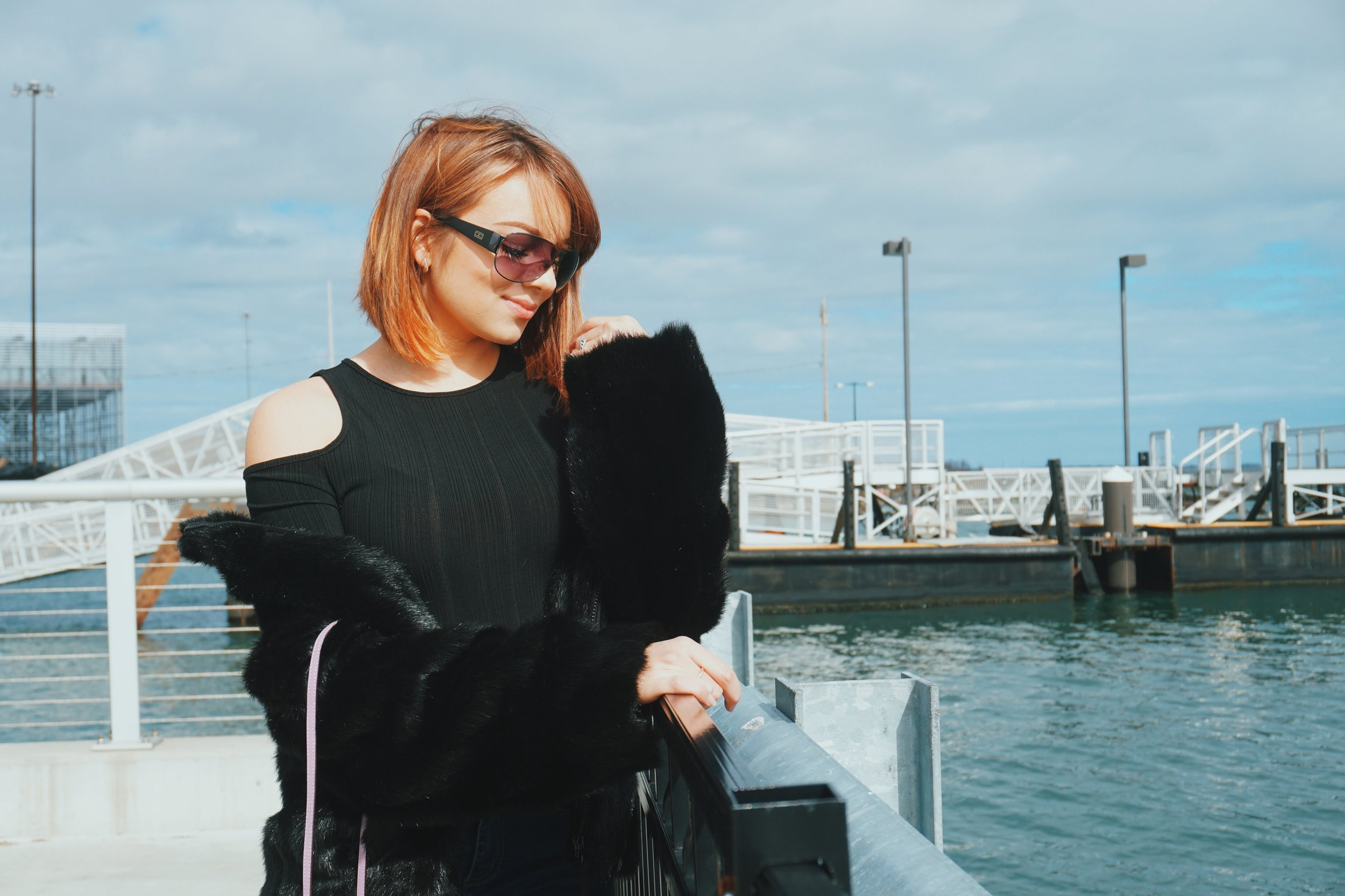 A blogger wearing an all-black outfit, posing by the ocean.