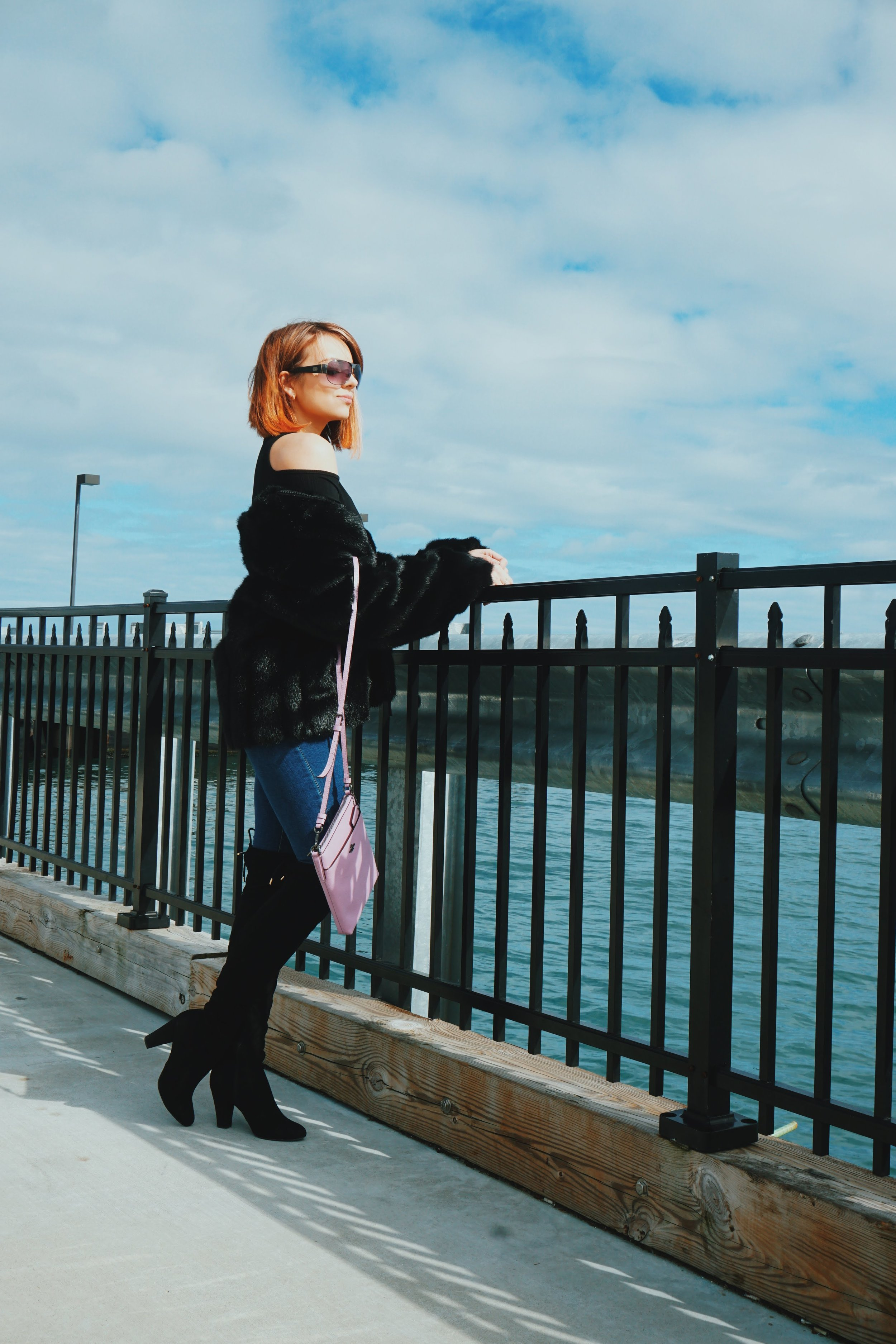 Blogger looking at the ocean, wearing black faux-fur coat, black OTK boots, jeans, and a pink Coach crossbody bag.
