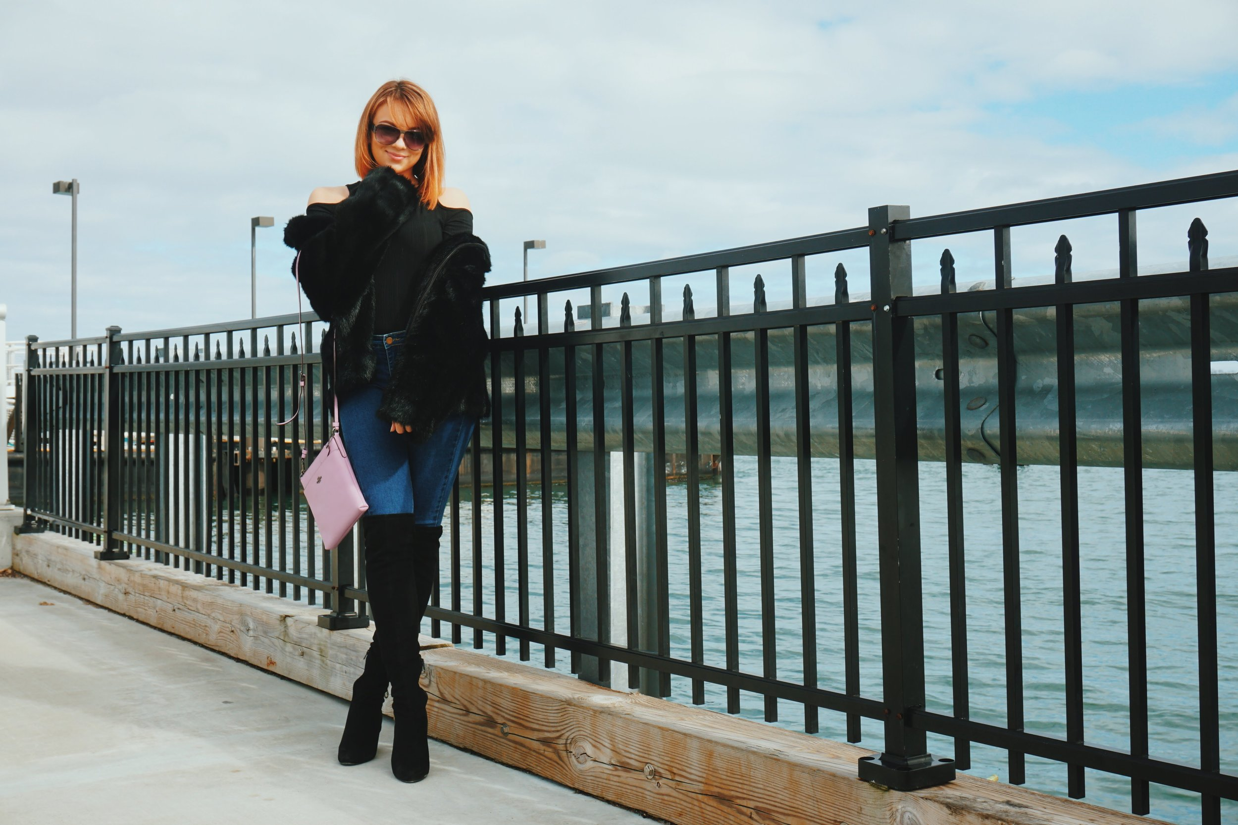 Lifestyle blogger posing near the ocean, wearing a black faux-fur coat, jeans, over-the-knee black boots, black shirt with open shoulders, and a Coach blush crossbody bag.