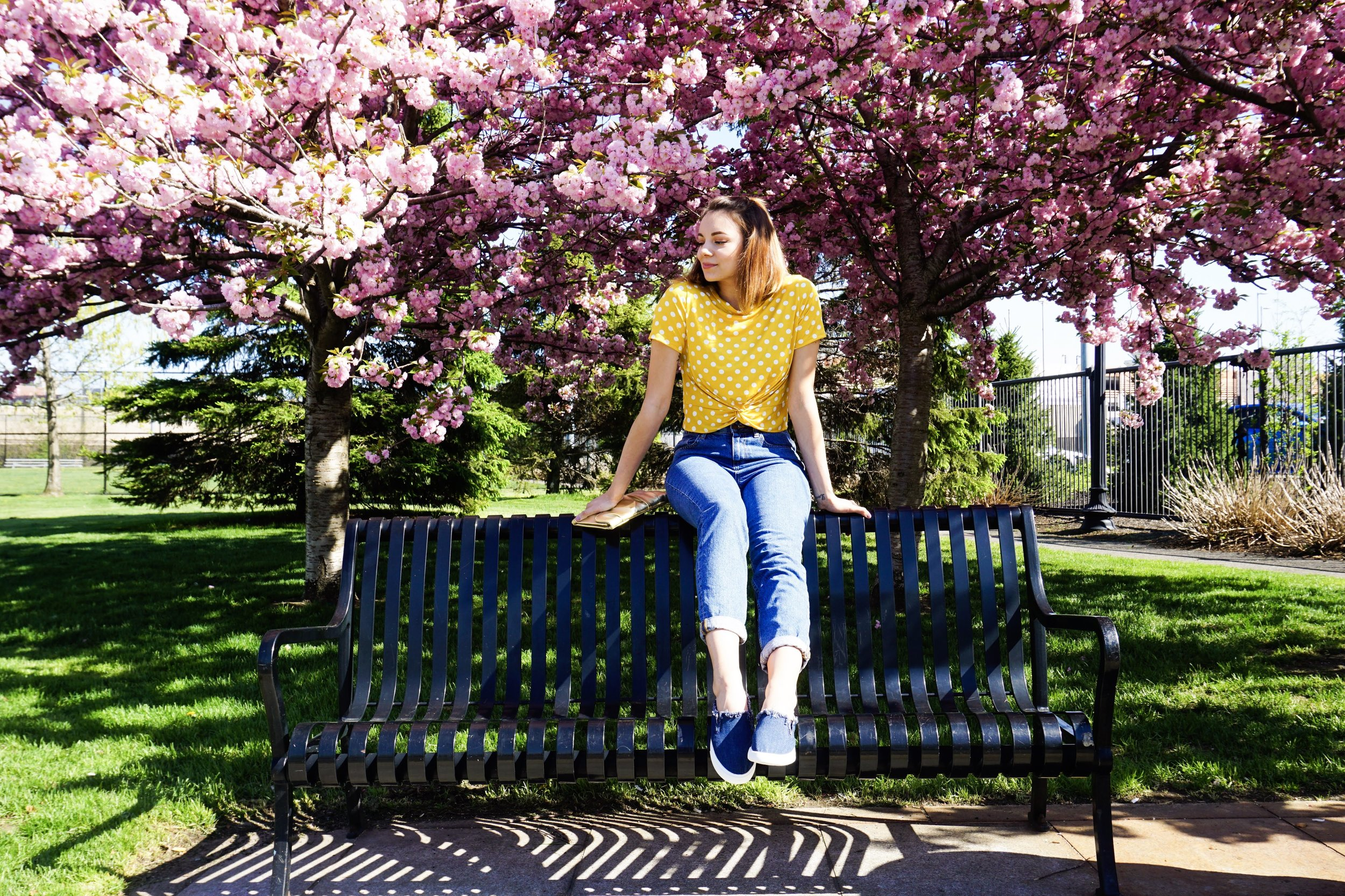 A girl is sitting on a bench in the park, wearing a yellow crop top, jeans, and denim slip ons.