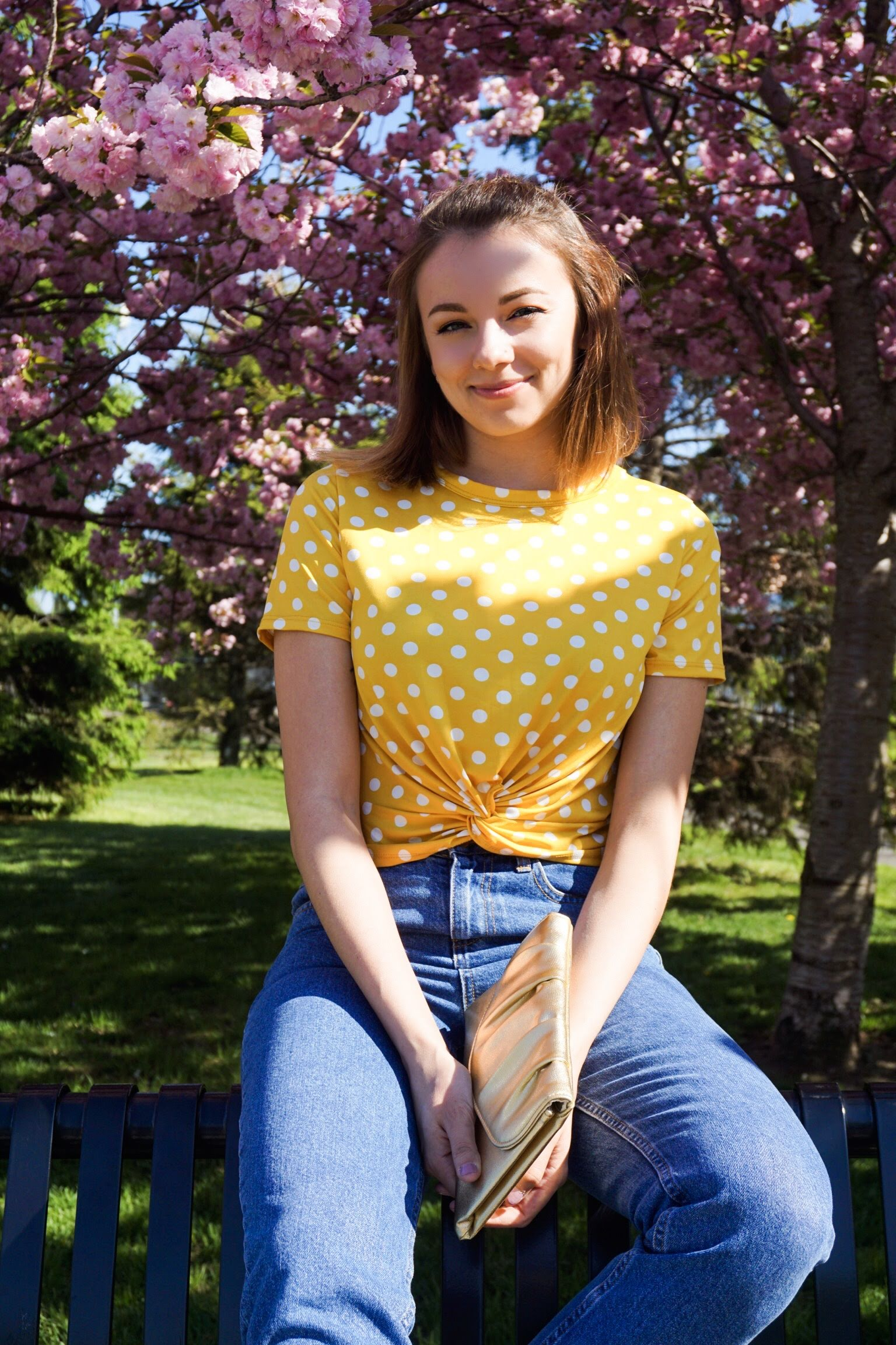 Fashion blogger looking at the camera, wearing a yellow and white polka dots crop top, blue denim jeans, and a golden clutch.