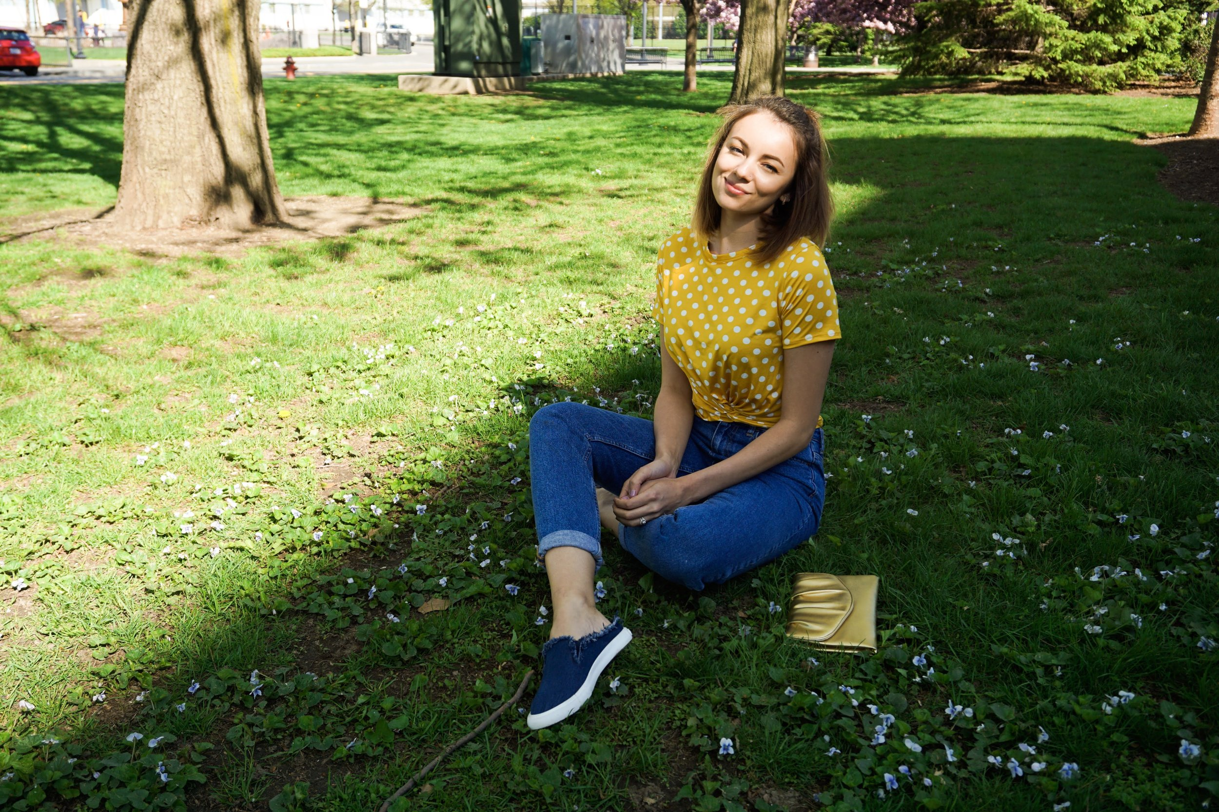 Blogger sitting on the grass, wearing a yellow and white polka dot crop top, mom jeans, denim slip ons, and a golden clutch.