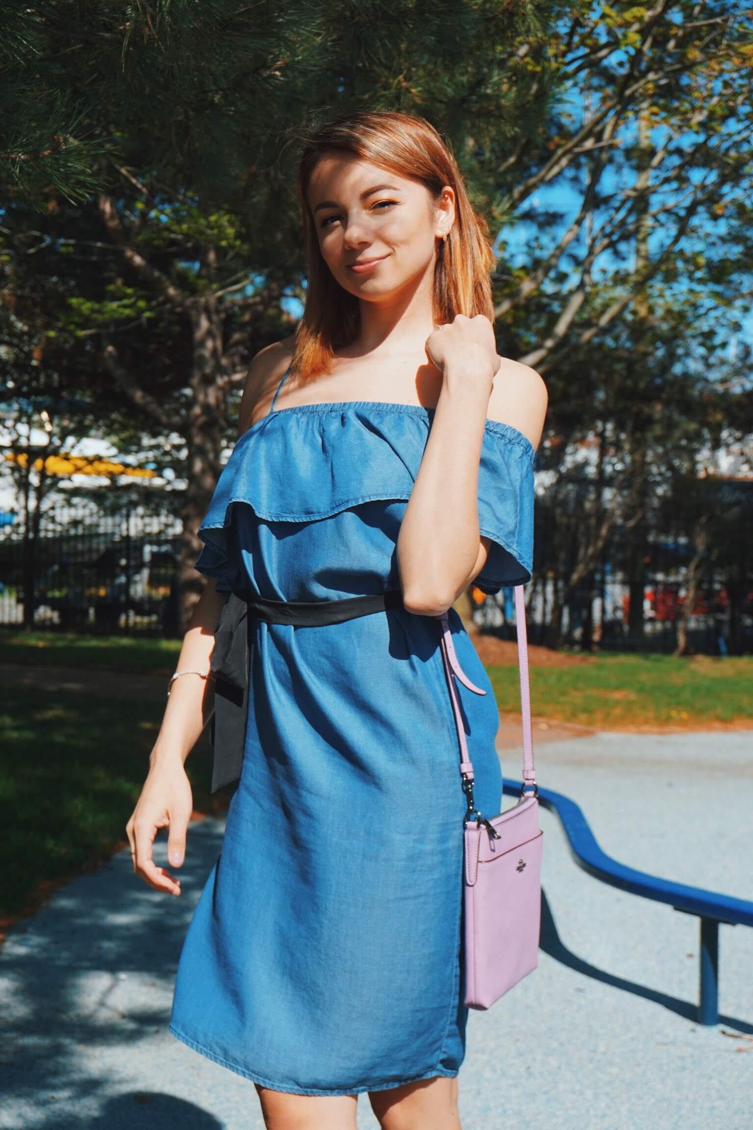 A girl wearing a cute denim summer dress, and a lilac Coach bag.