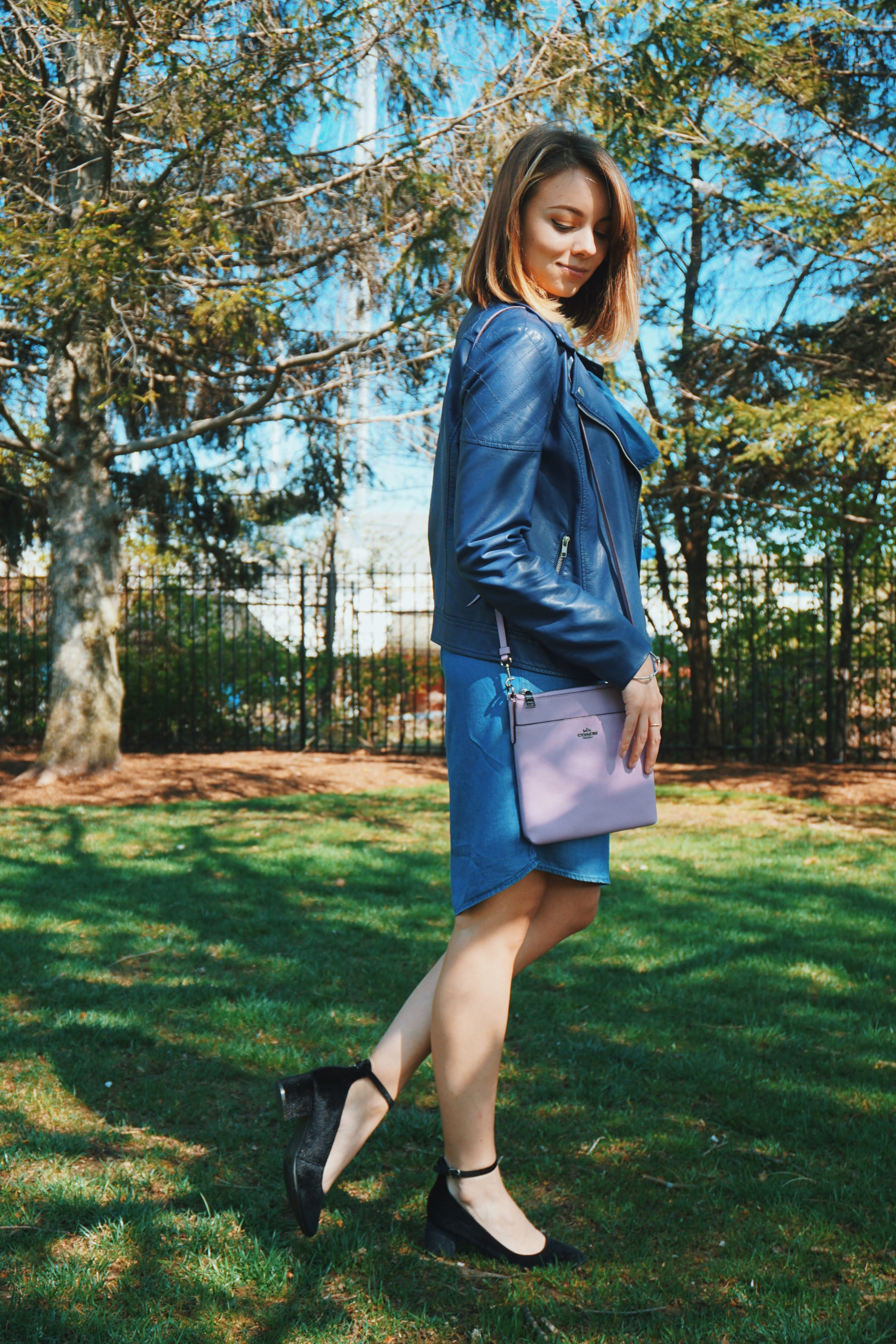 A girl standing on a grass, wearin a denim blue dress, blue faux leather jacket, lilac Coach purse, and black Unisa pumps.