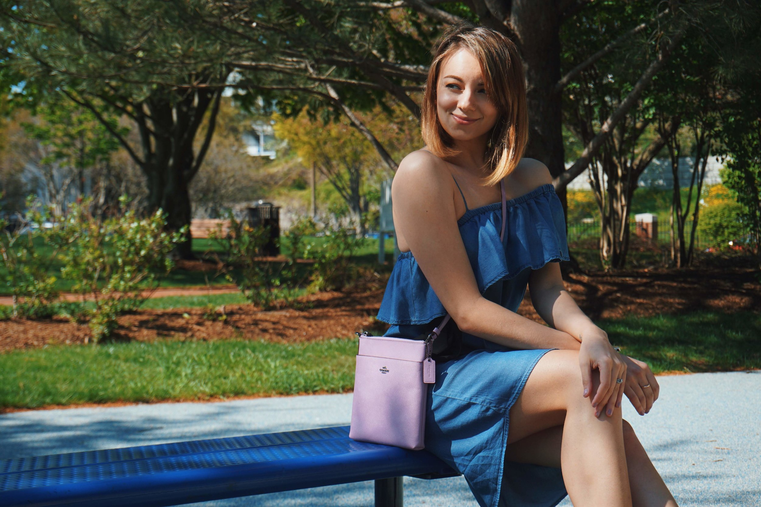 A blogger sitting on a bench in a cute summer outfit: denim dress, lilac purse.