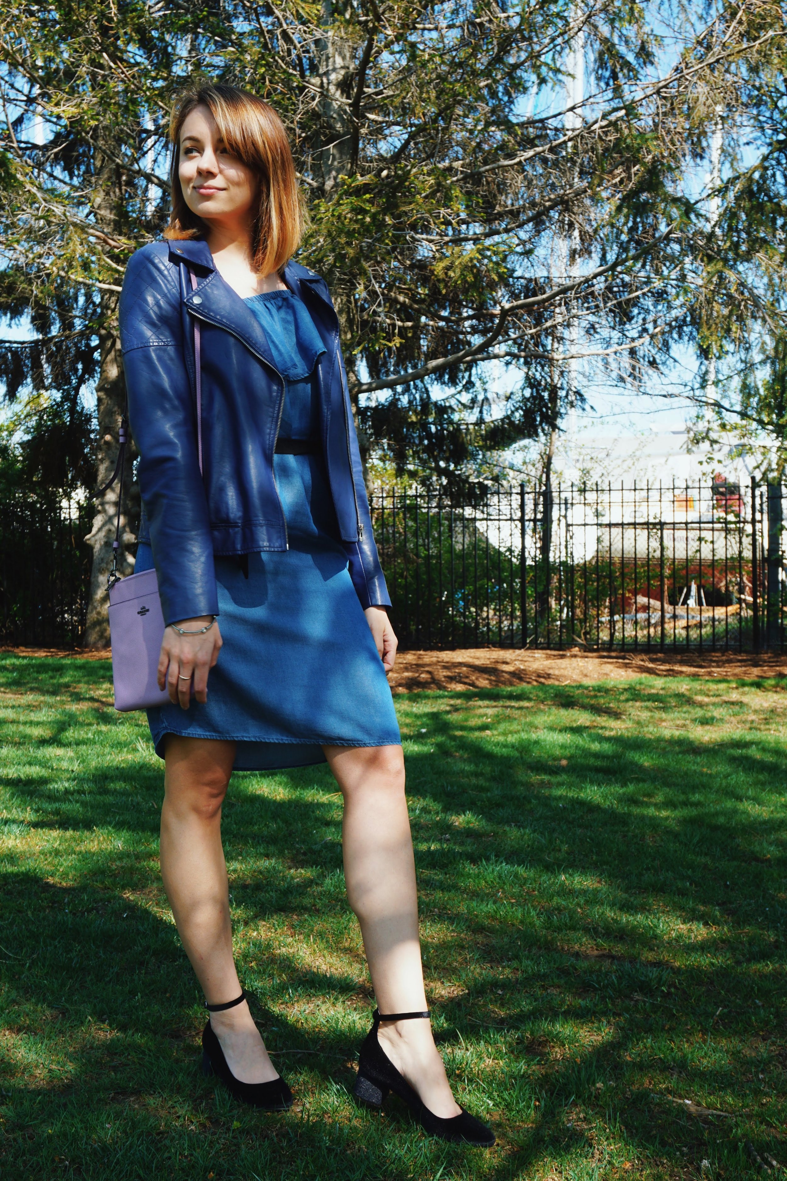 A girl in the park, wearing a denim dress, blue faux leather jacket, black pumps, and a lilac bag.