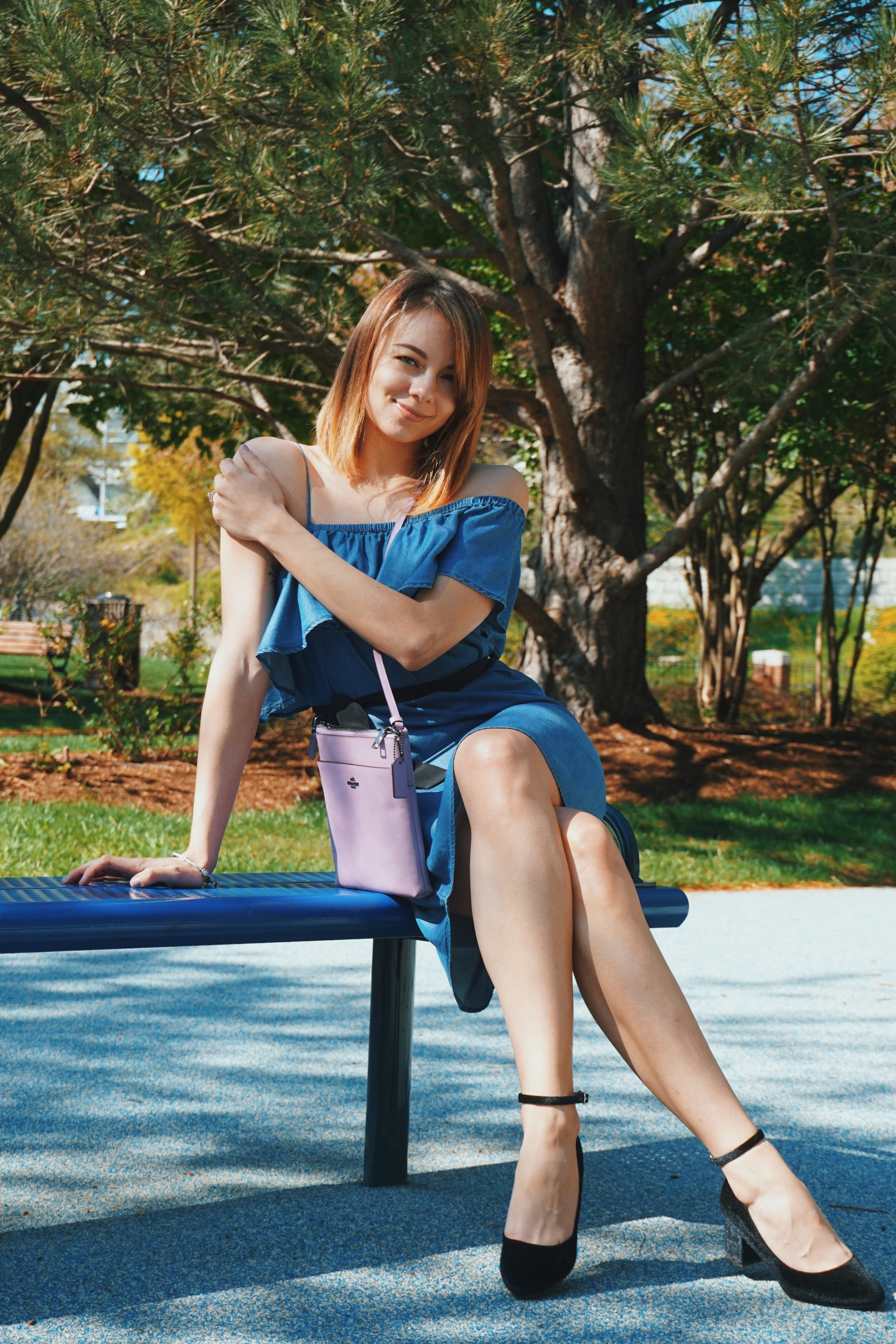 A fashion blogger sitting on a bench wearing a denim dress with ruffles on the chest area, black Unisa pumps, and a lilac Coach bag.
