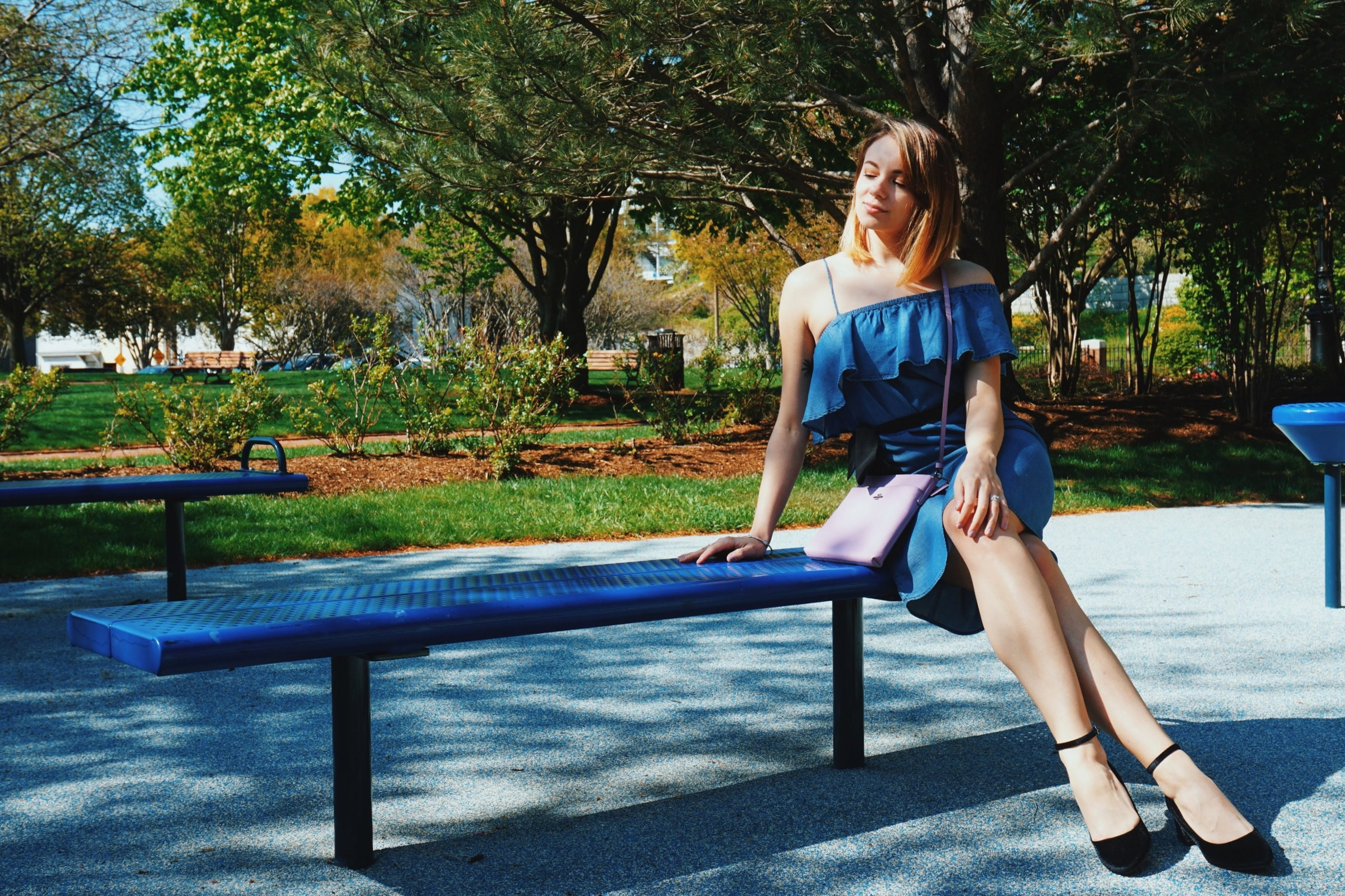 A girl sitting on a bench wearing a cute summer outfit: denim dress, black pumps, and a lilac purse.