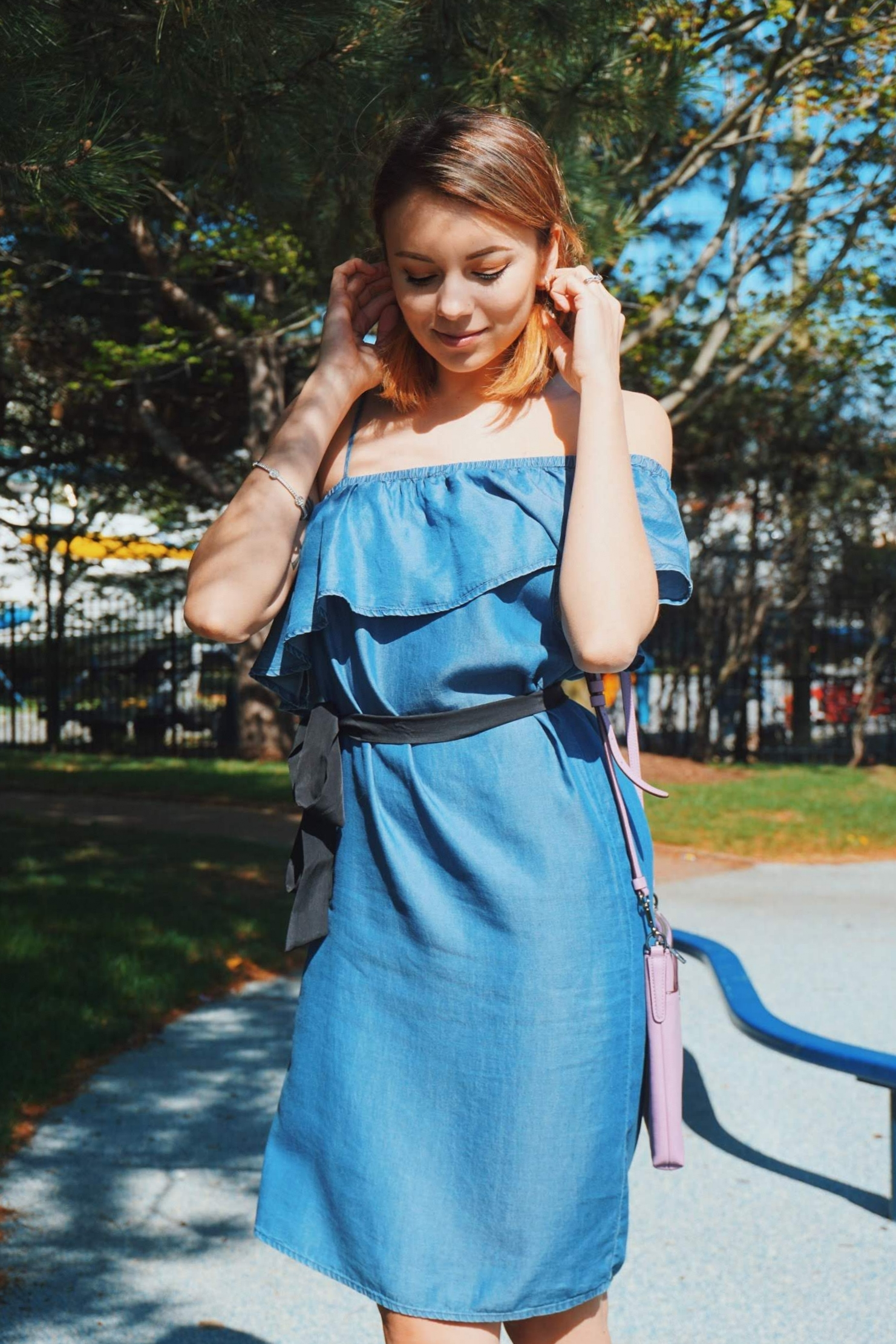 A girl wearing an adorable denim dress with ruffles on its top, one shoulder is open, black tie on the waist.