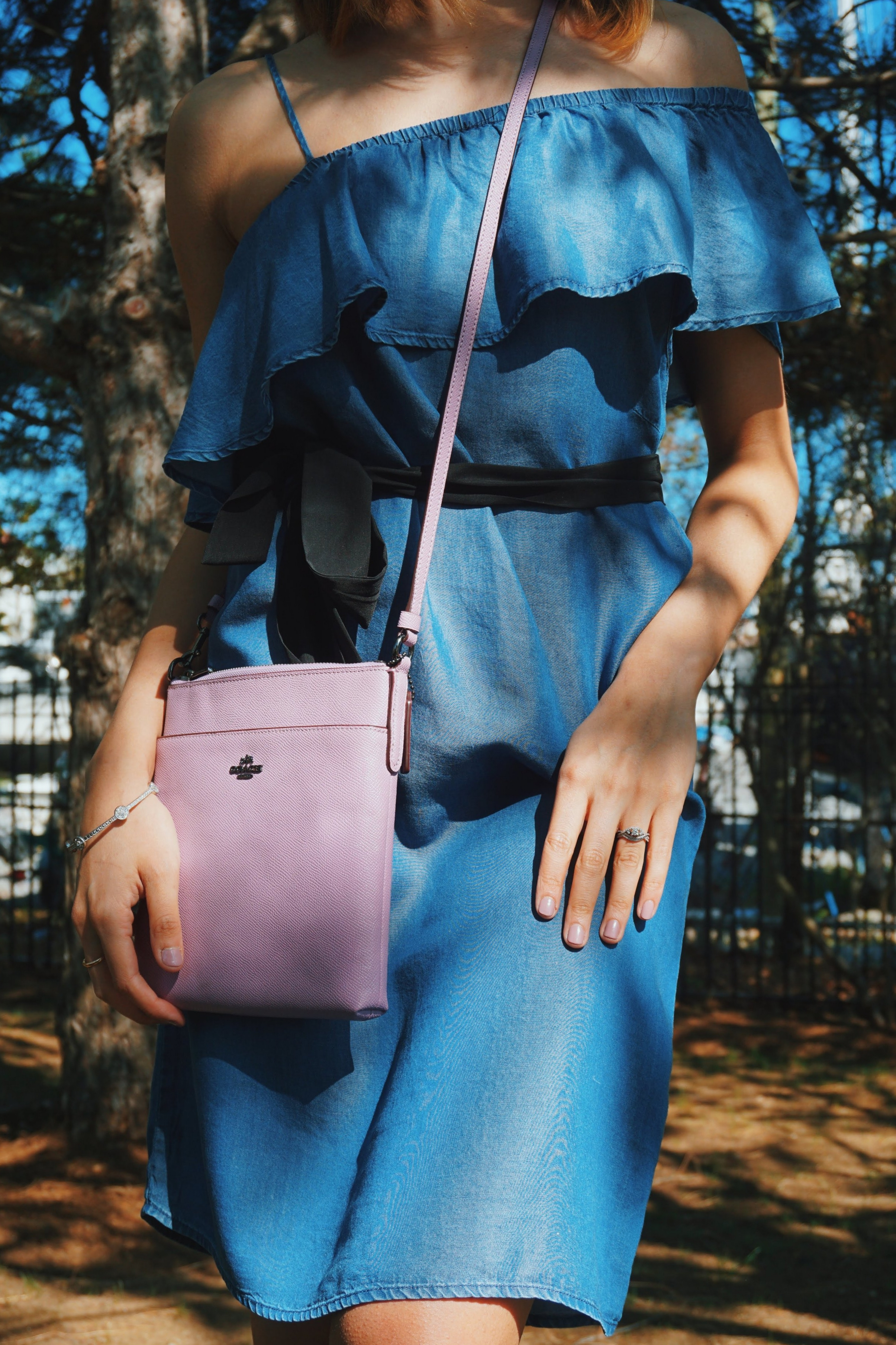 Detail shot of a summer outfit: blue denim off-the-shoulder dress, black tie on the waist, ruffles on the top, and a lilac Coach bag.