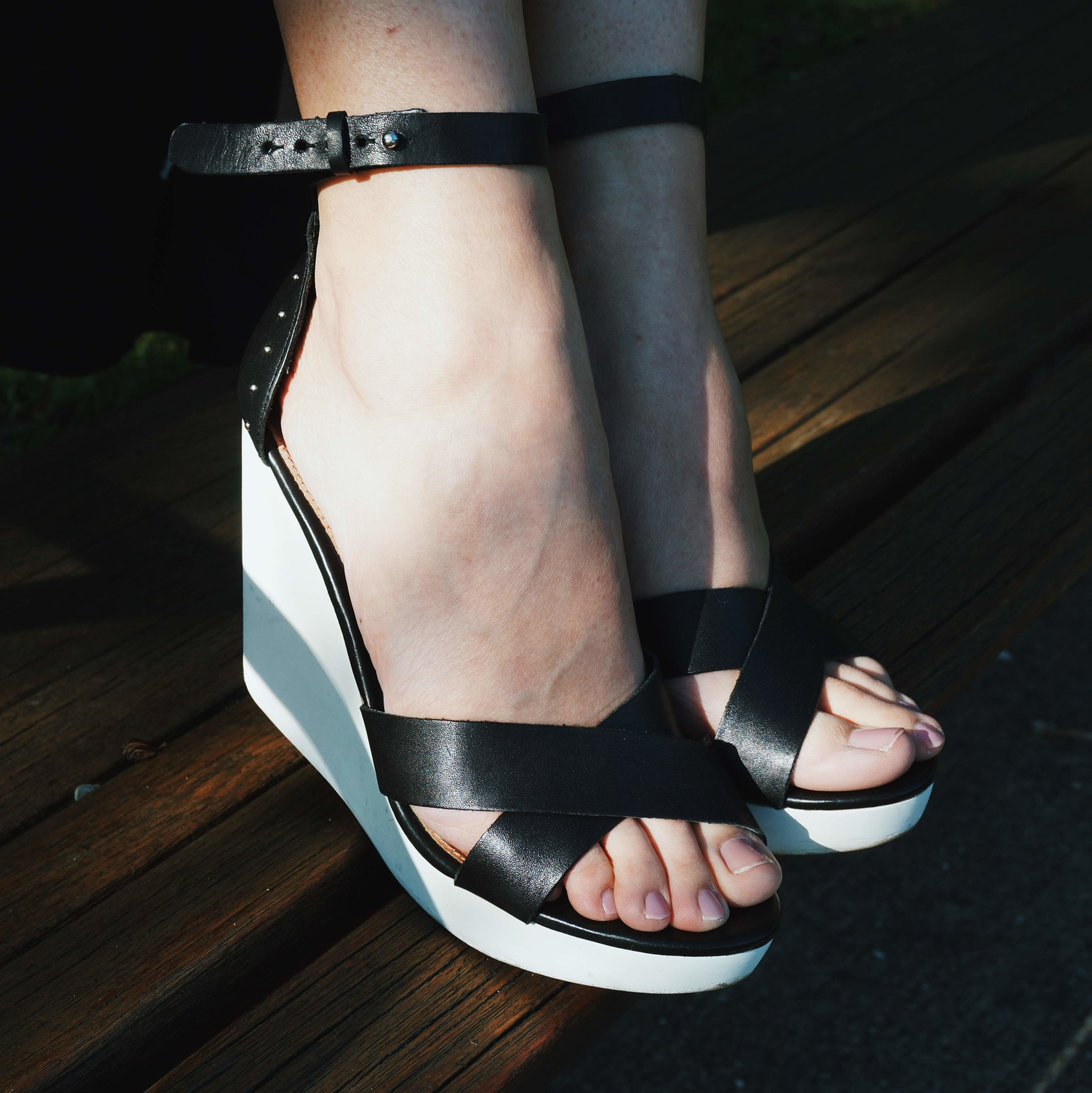A photo of shoes: black and white wedges.