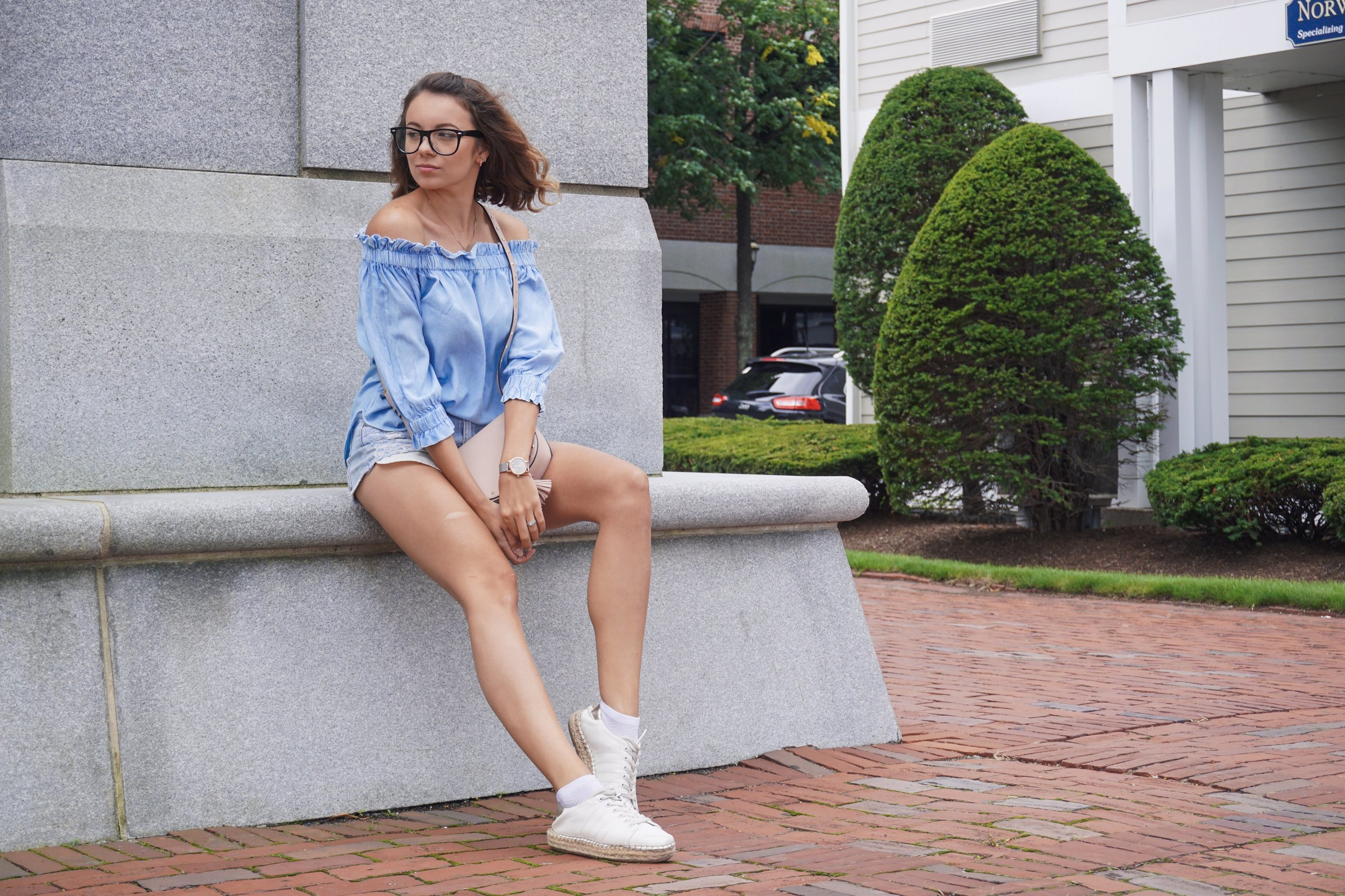 A fashion blogger sitting near monument and wearing denim shirt, denim shorts, white sneakers, and pink little bag.