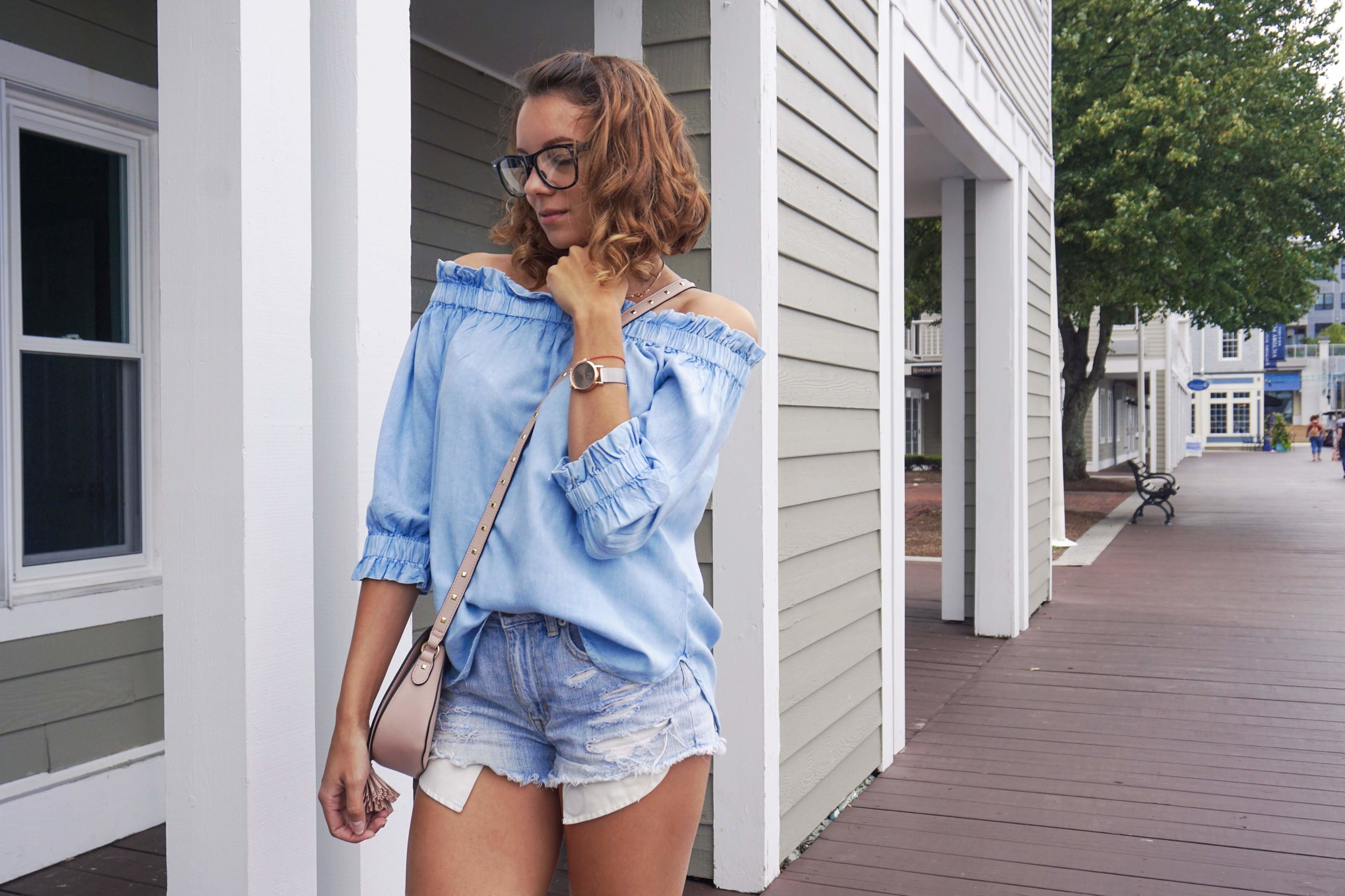 A fashion blogger posing near houses, wearing an all denim outfit.