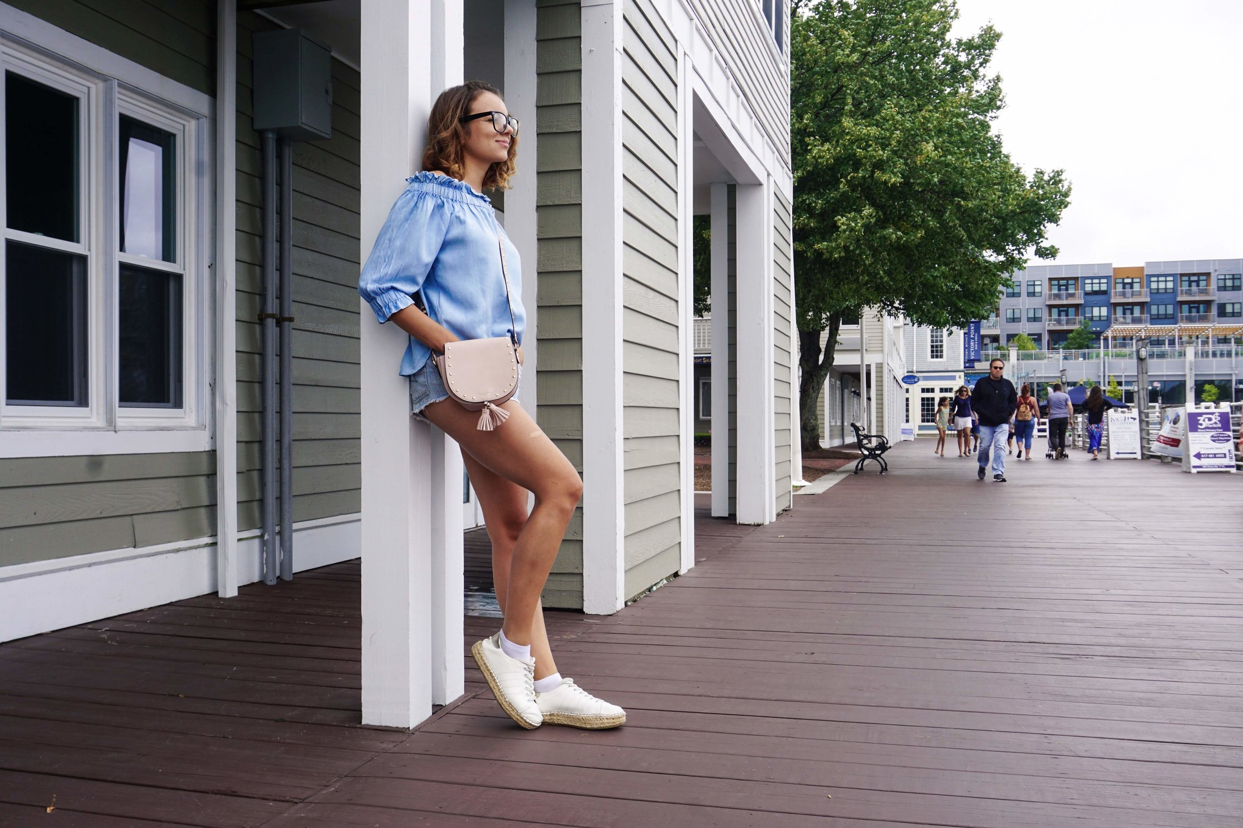 A photo of a blogger posing on the street near house, wering an all denim summer look.