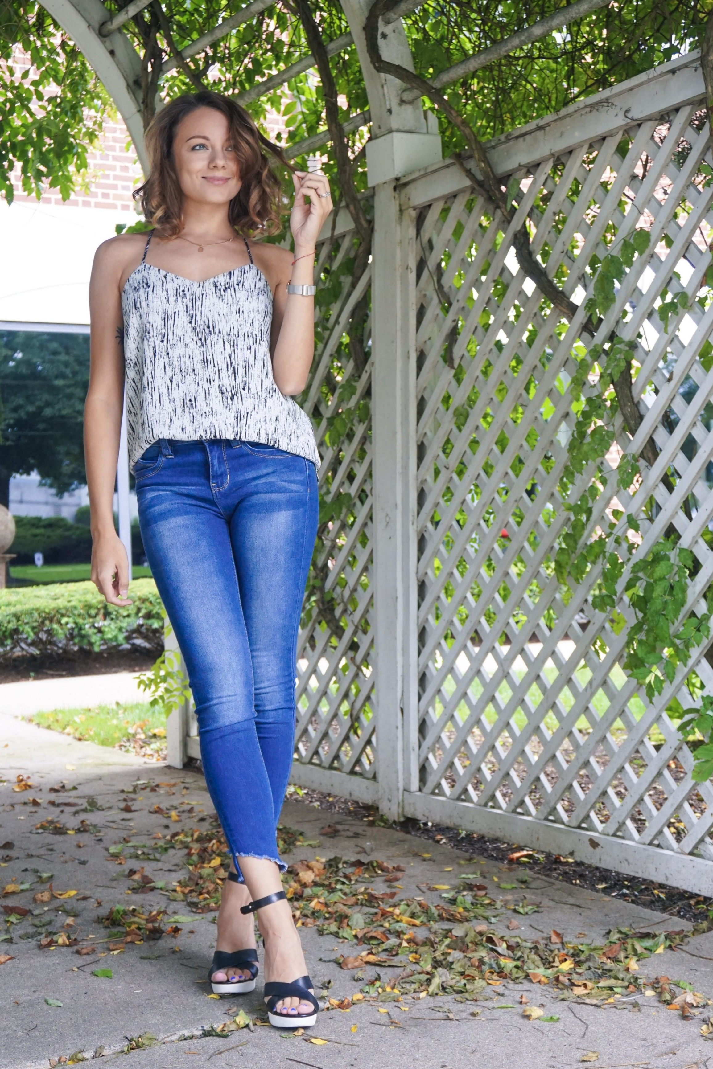 A fashion blogger wearing denim capris, black and white tank, and black and white wedges.