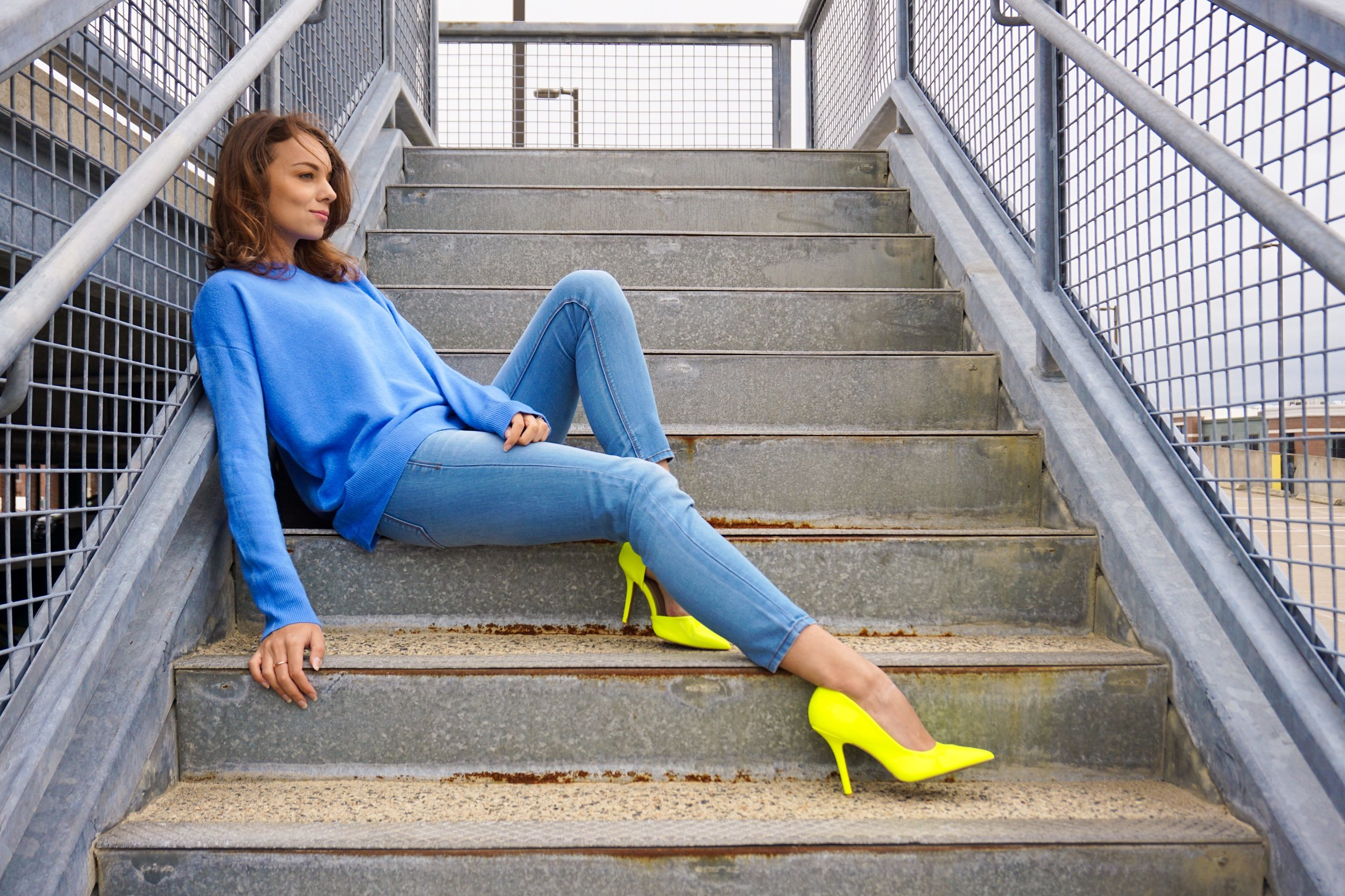 A fashion blogger sitting on the steps looking away from the camera, wearing a blue sweater, light blue jeans, and neon heels.