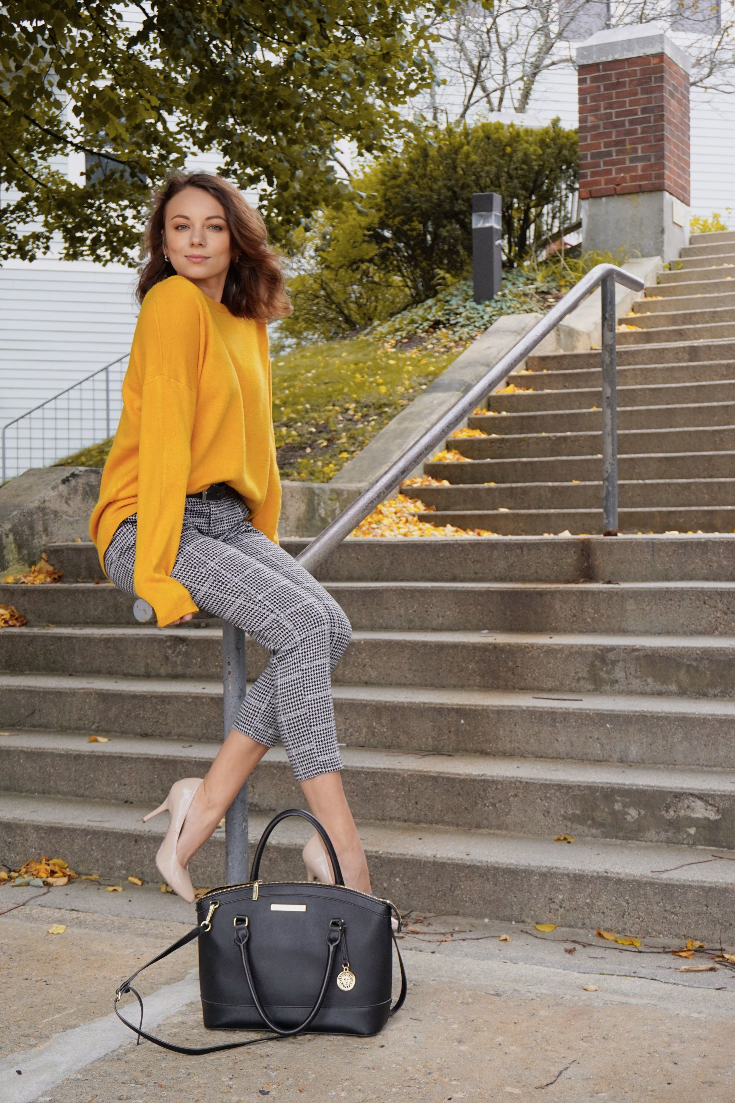 A girl sitting on a set of stairs outside, wearing a mustard colour sweater, white and black capris, nude heels, black purse.