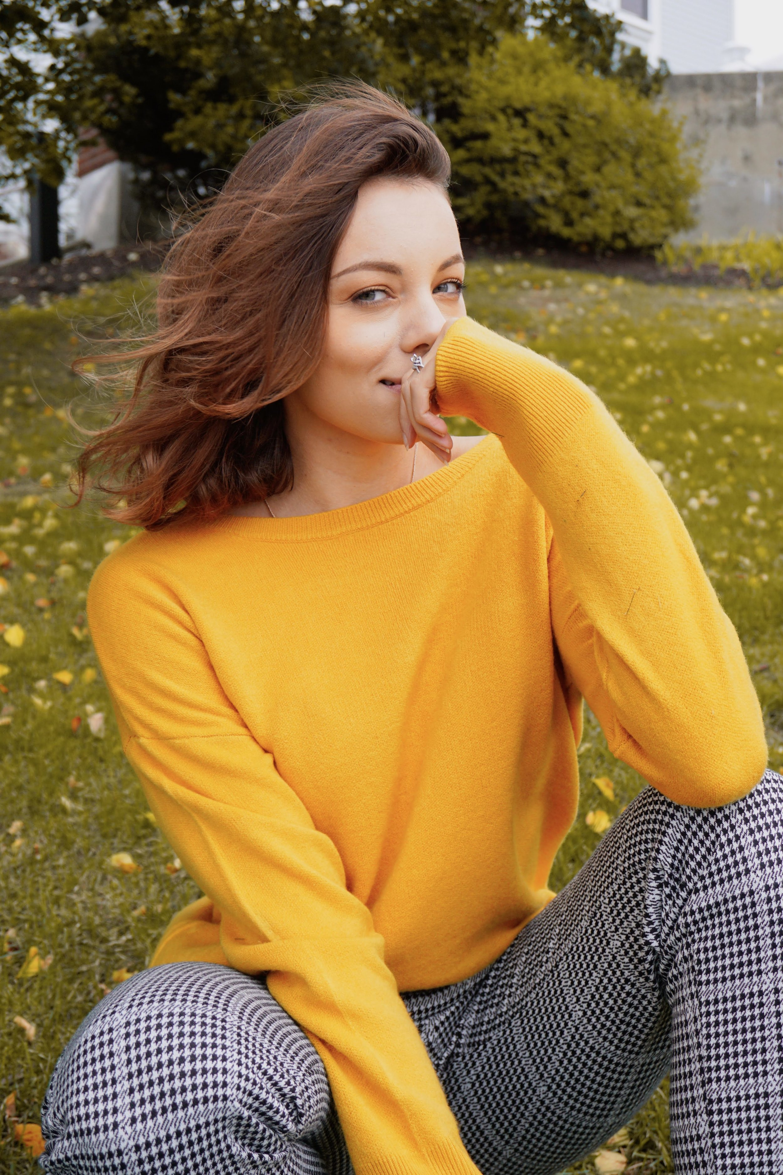 A portrait of a blogger who is wearing a mustard colour sweater and black and white pants.