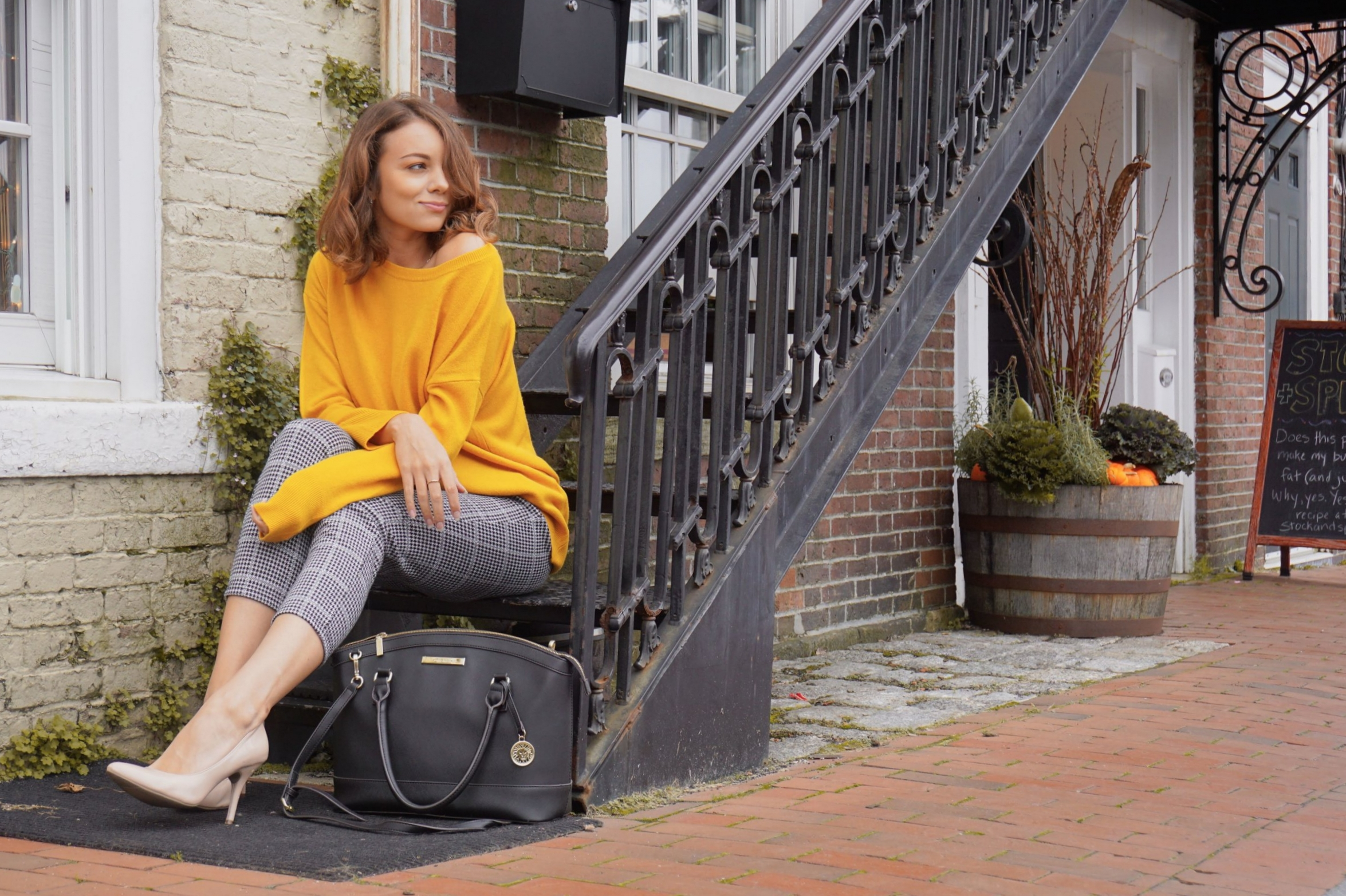 A blogger sitting on stairs near a brick buildin wearing mustrd sweater, houndstooth pants, nude pumps, and black bag.