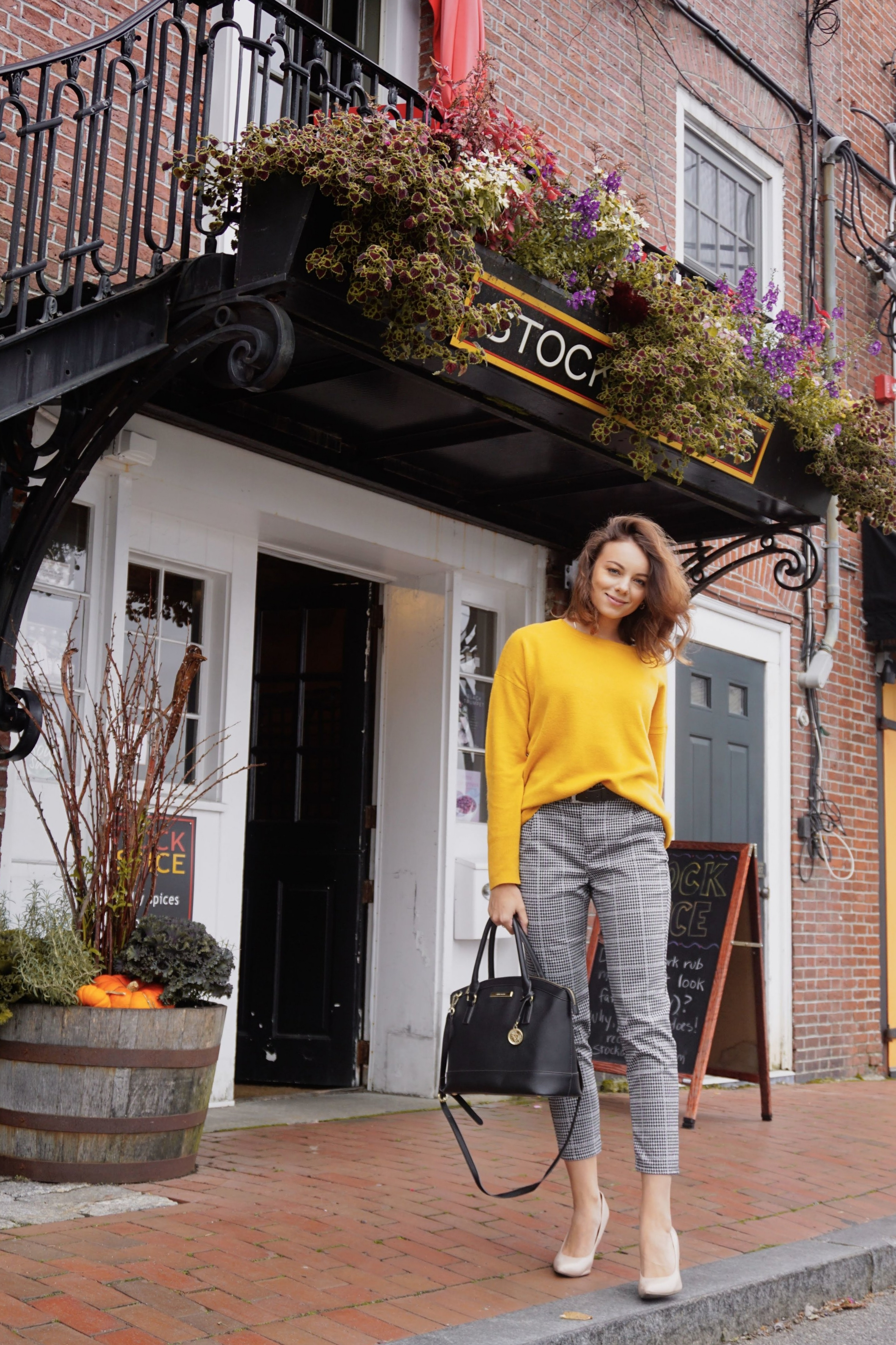 A blogger standing on a street near a brick building wearing an autumn outfit.