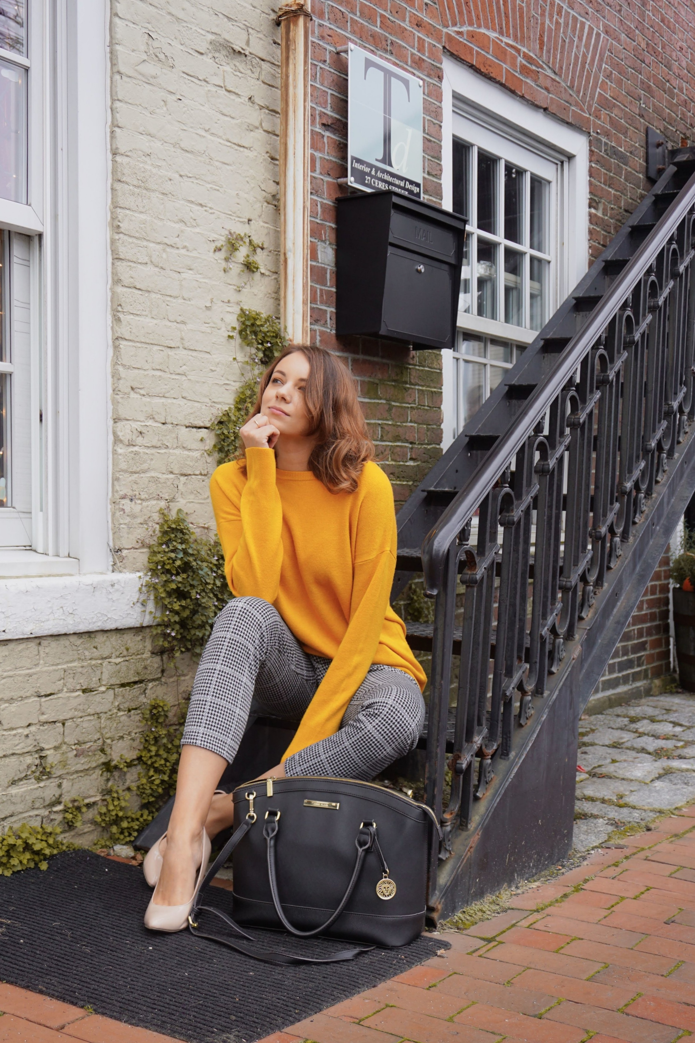A fashion blogger sitting on steps near a building wearing a mustard sweater, black and white pants, nude pumps.