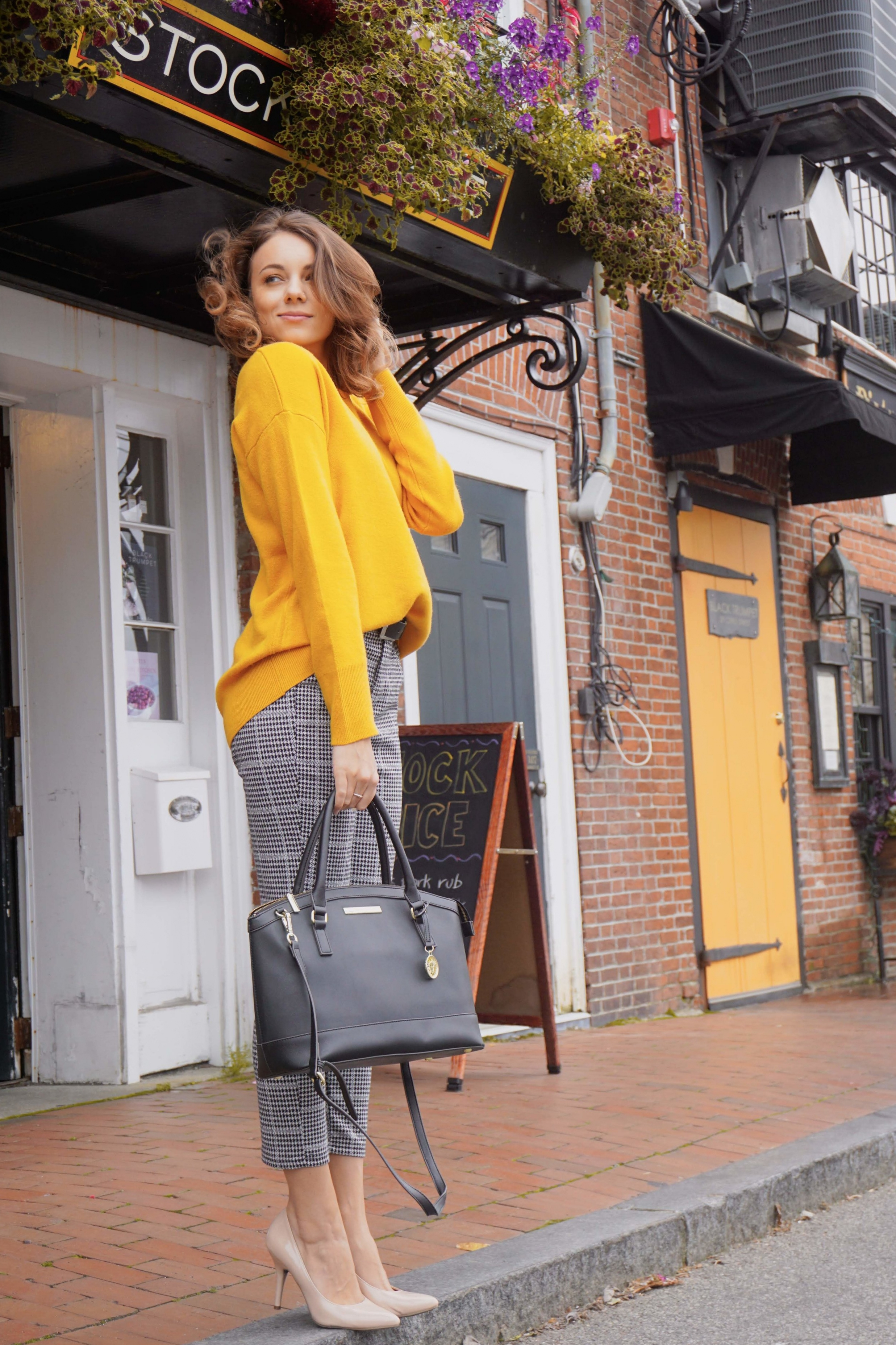Autumn outfit inspiration: mustard colour baggy sweater, black and white pants, nude pumps, and black bag.