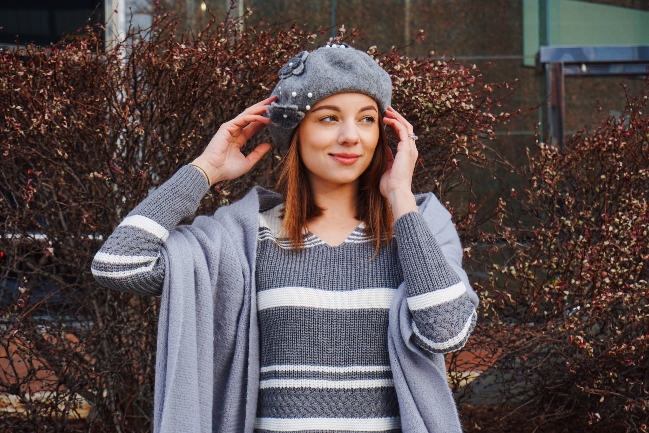 A portrait of a girl wearing a gray and white sweater, gray scarf, and gray beret.