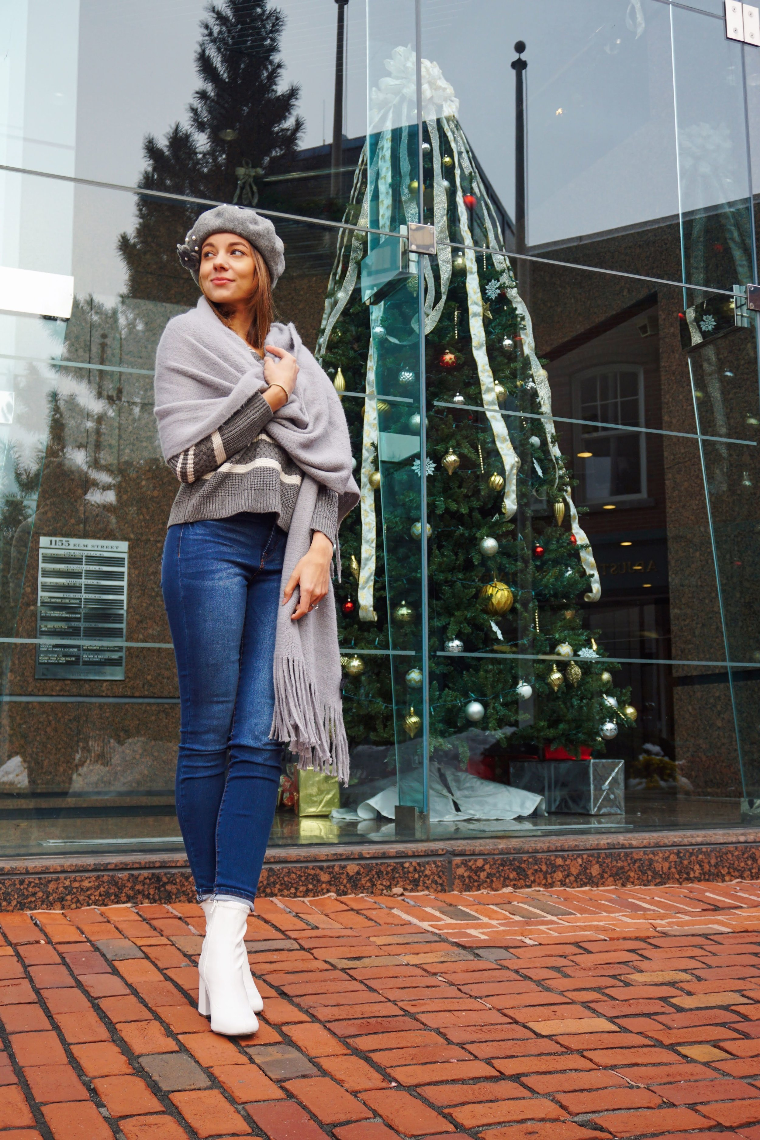 A photo of a blogger standing in front of a building mirror and Christimas tree.