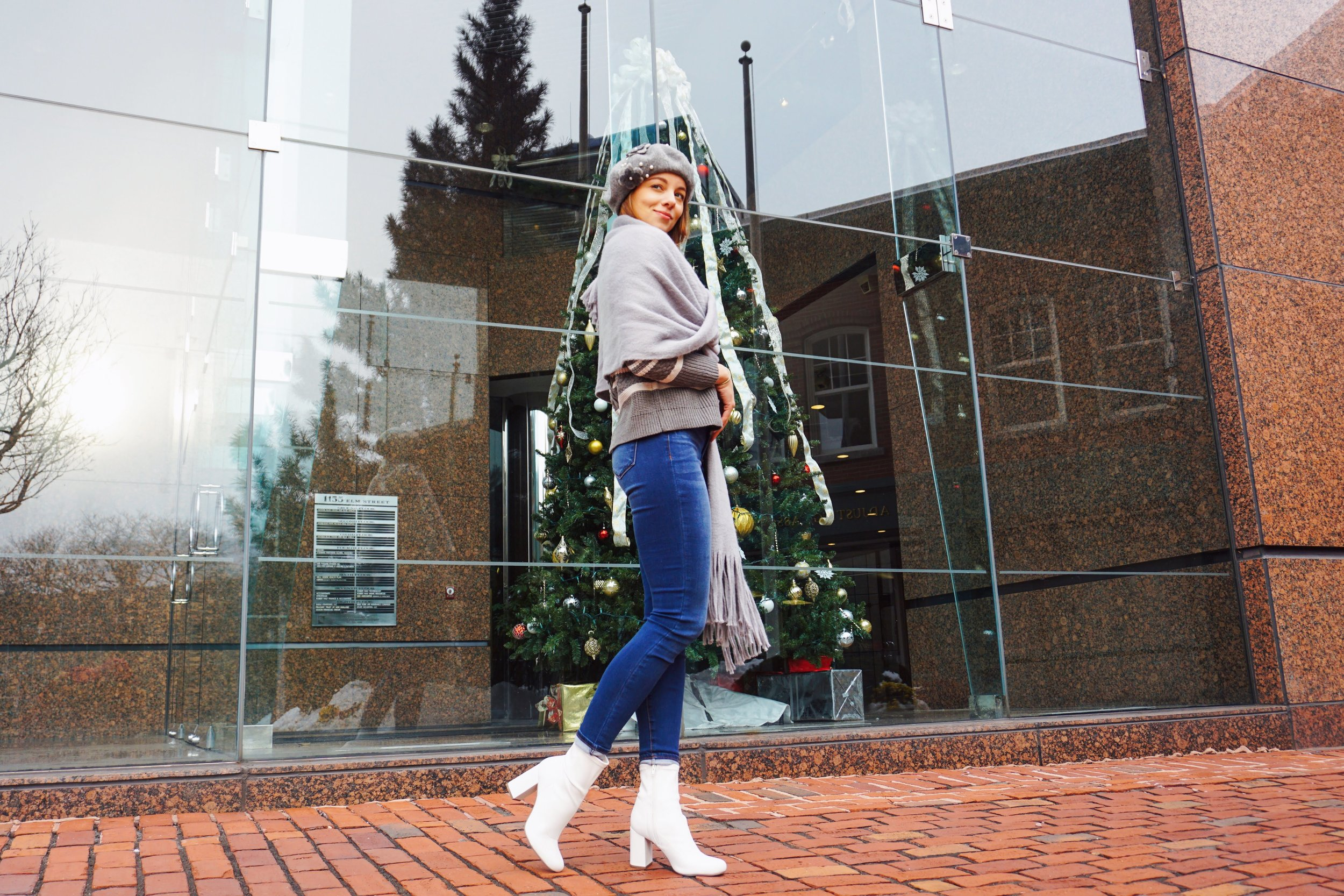 A photo of a girl posing near a Boston building, wearing a gray and white sweater, gray scarf, gray beret, blue denim jeans, and white booties.