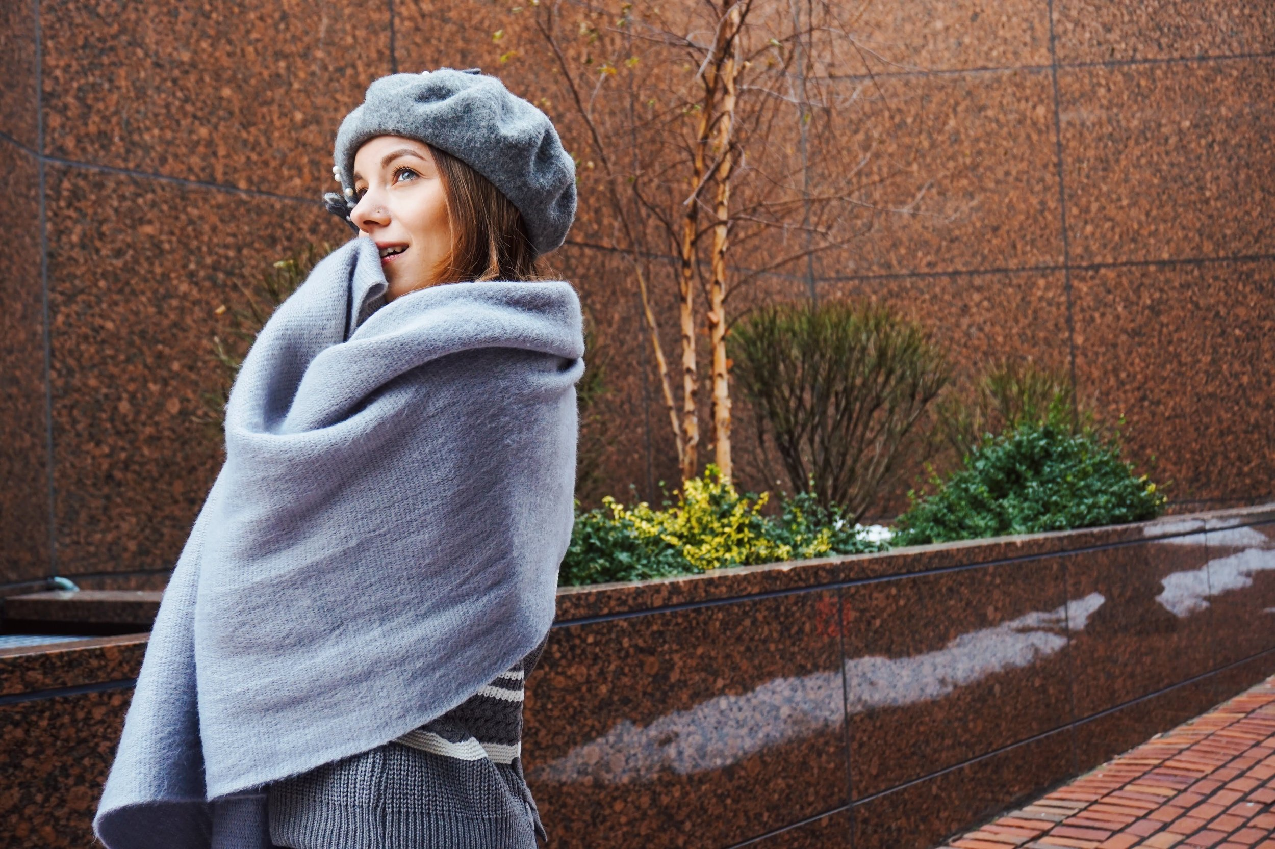 Blogger looking up, wrapped around in a gray sweater, wearing gray beret on her head.
