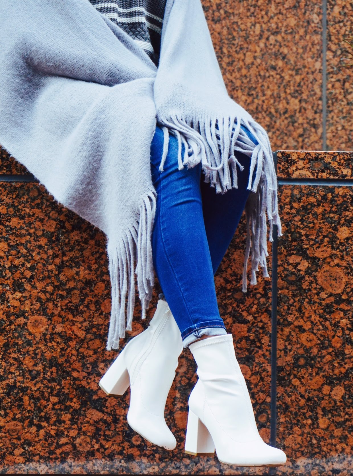 A detailed shot of an autumn outfit, blue denim jeans. gray sweater and gray scarf, white booties.