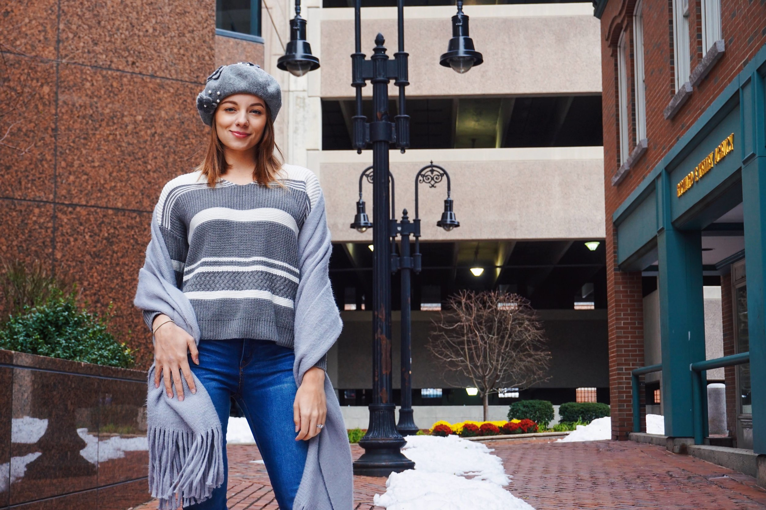 A photo of a lifestyle blogger in Boston who is wearing a gray sweater with white stripes, gray scarf, blue denim jeans, and gray beret.