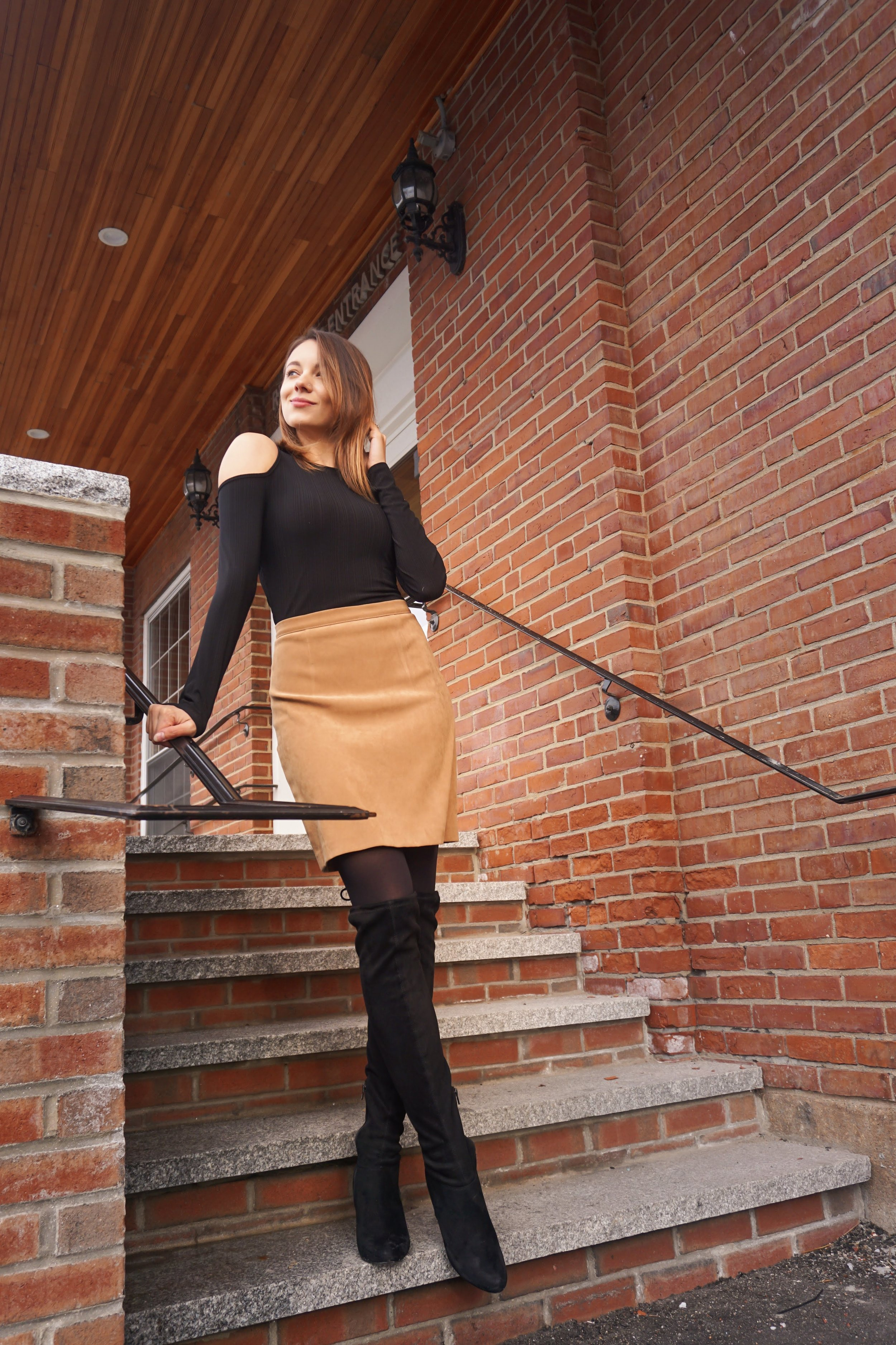 A blogger posing near a brick building wearing a black shirt with open shoulders, brown skirt, and black over the knee boots.