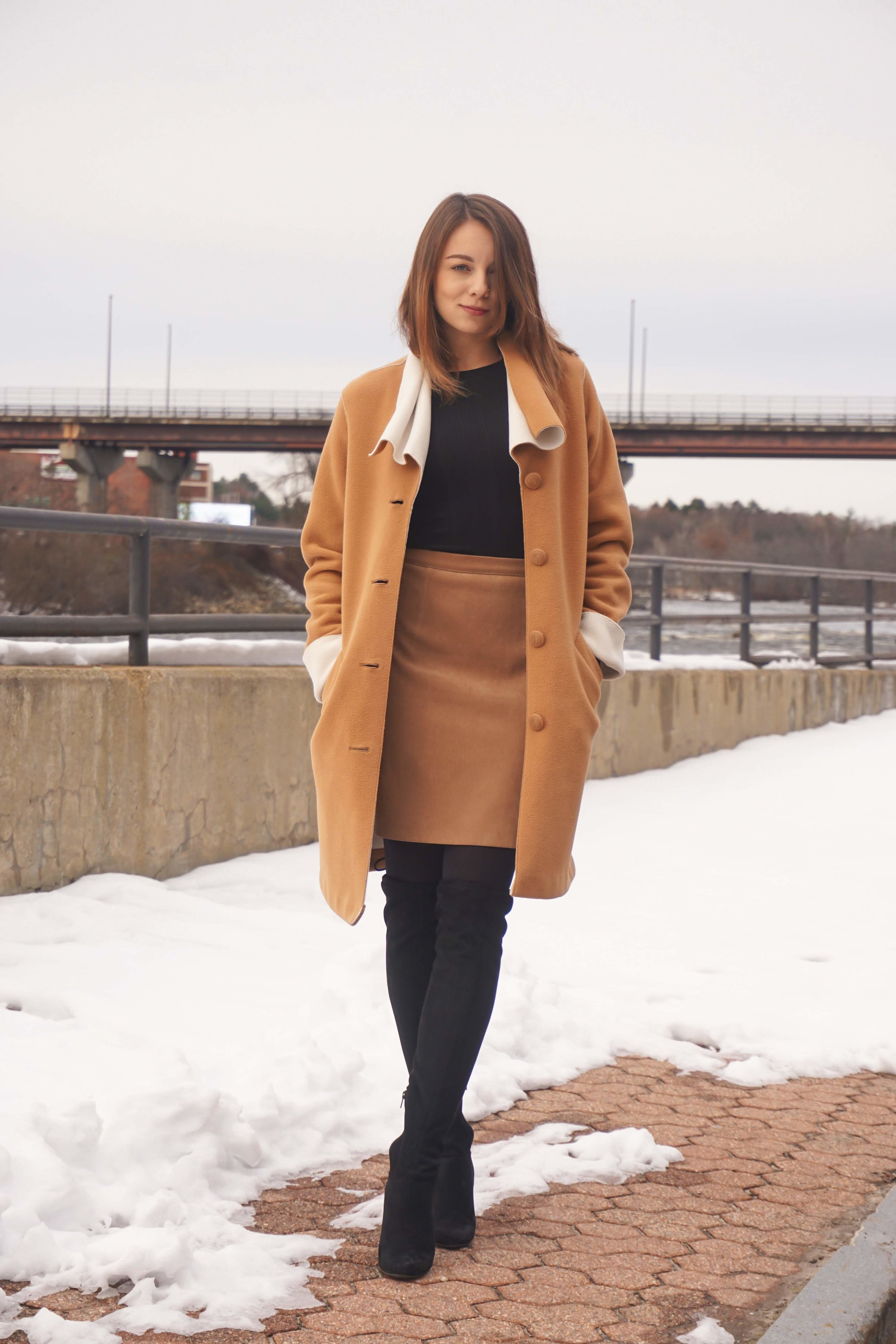 Fashion blogger posing near a river wearing a brown skirt, black top, brown coat, and black OTK boots.