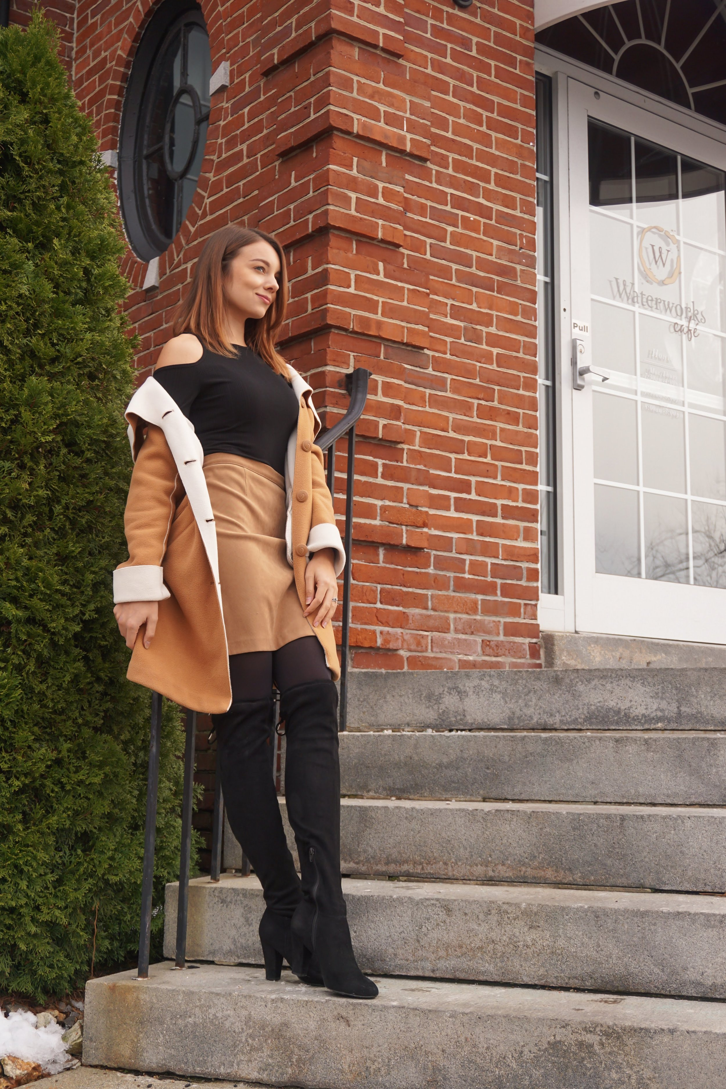 Lifestyle blogger posing on the stairs near a cafe, wearing a brown coat and skirt, black shirt, ,and black over the knee boots.