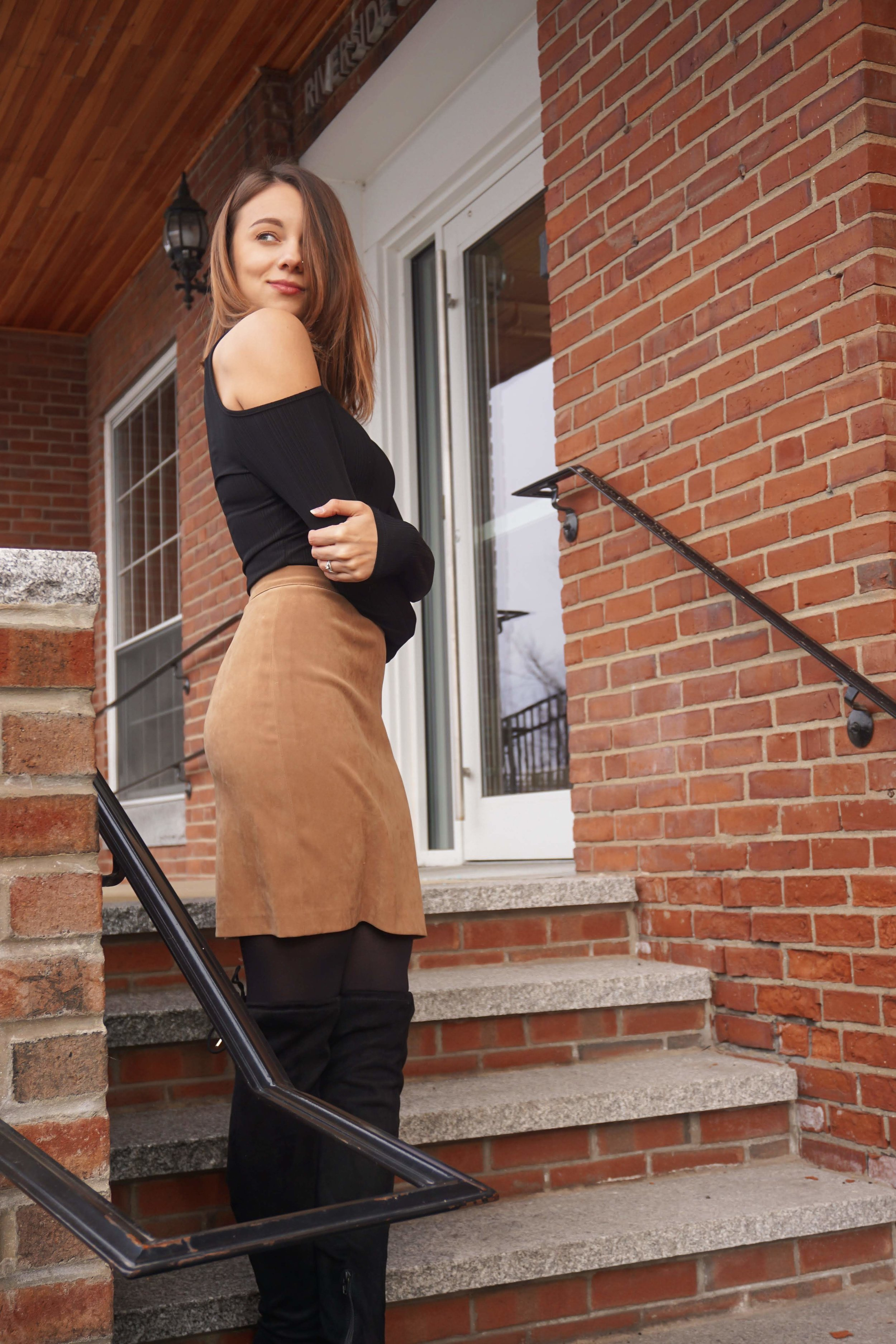 Blogger a cute romantic outfit while posing on the stairs near a brick building.