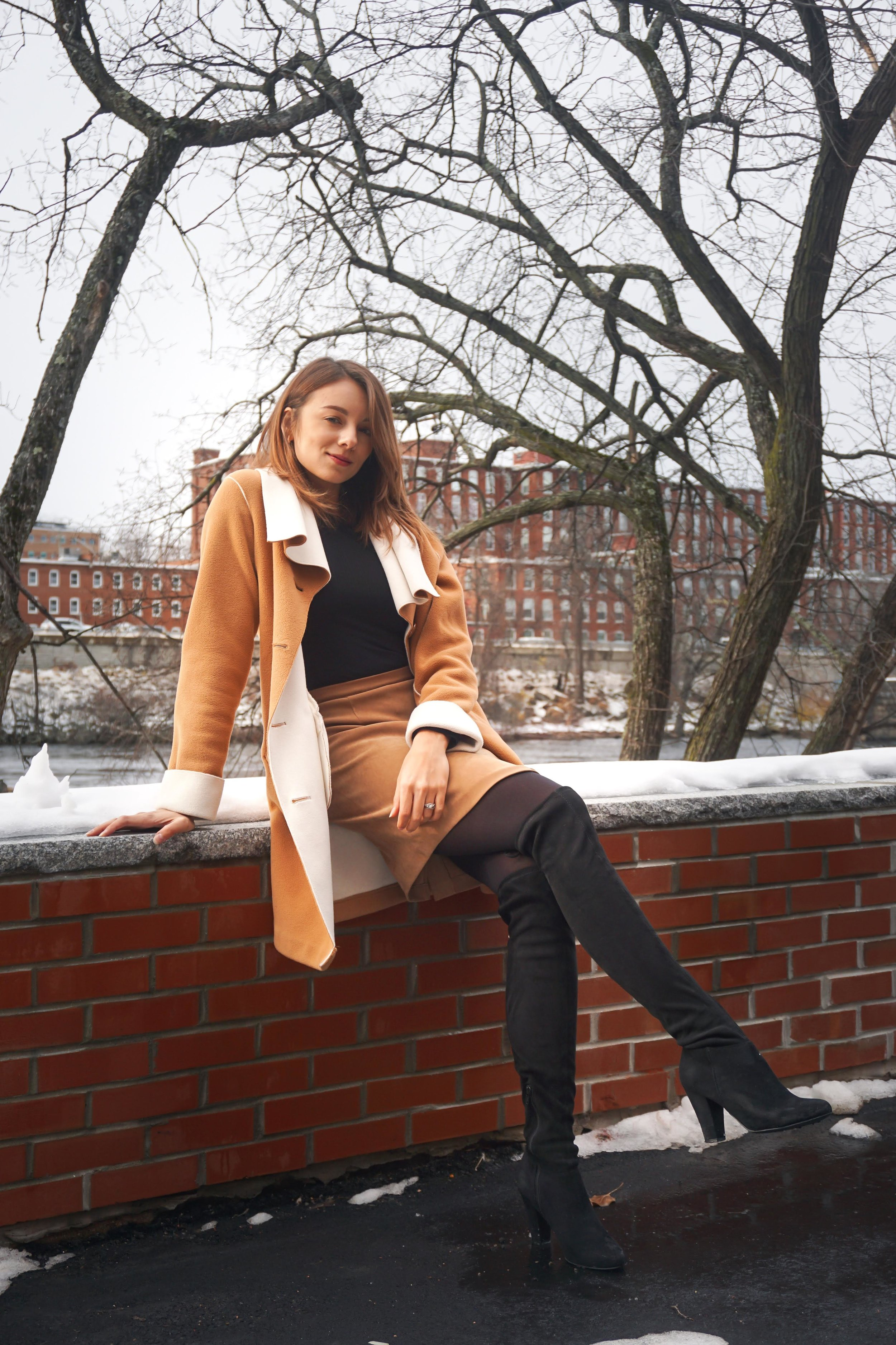 Blogger wearing a black and brown outfit while sitting near a river.