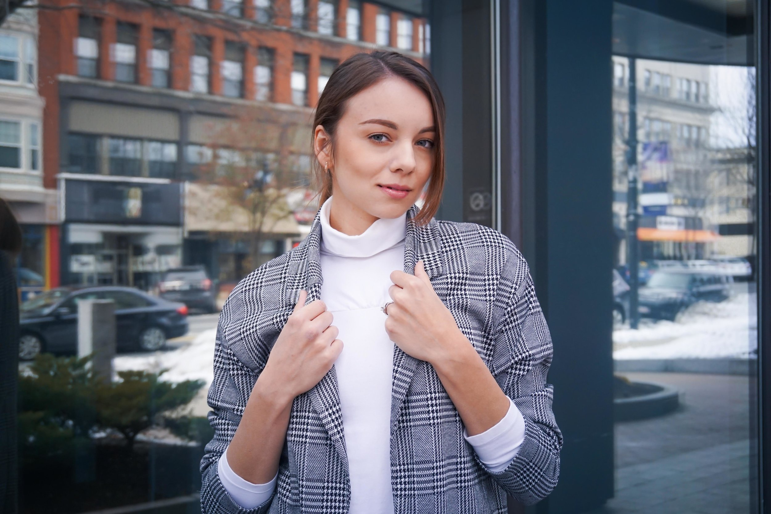 A portrait of a fashion blogger wearing a white turtleneck and houndstooth blazer.