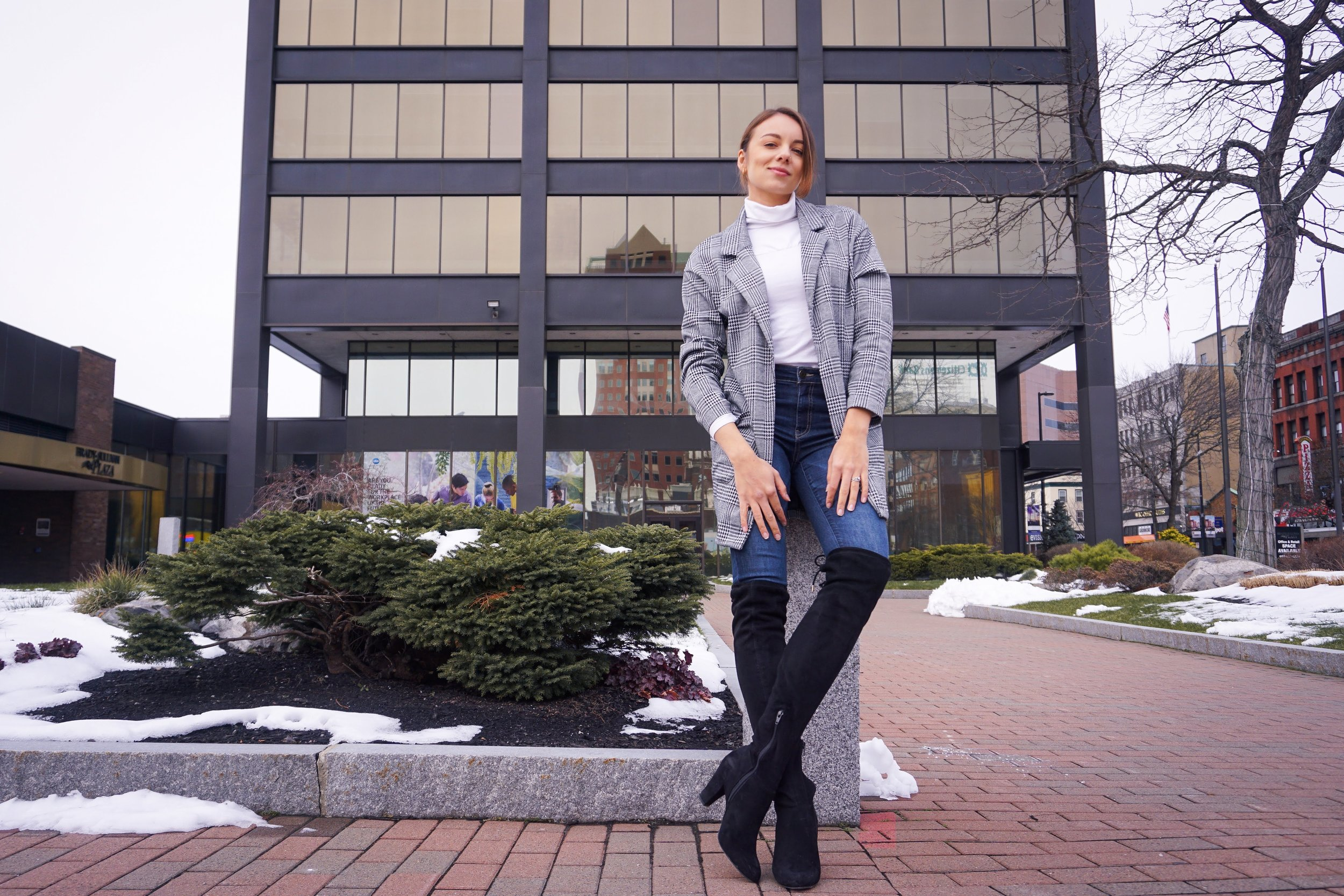 Fashion blogger posing near a glass building wearing a houndstooth blazer, white turtleneck, dark denim jeans, and black over-the-knee boots.