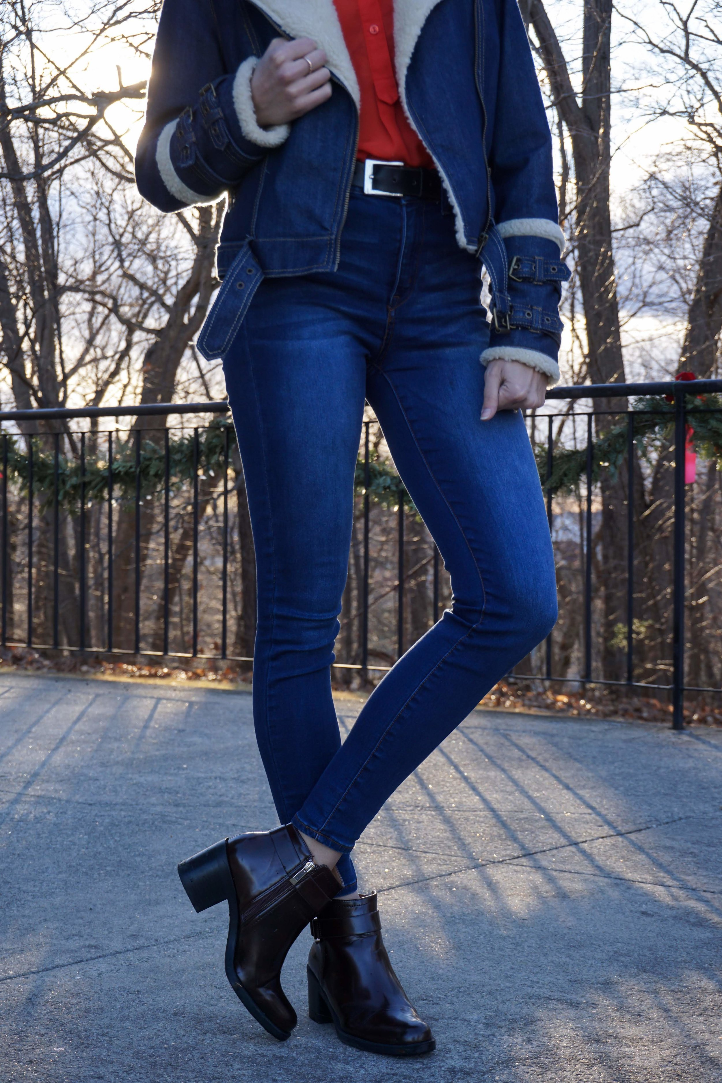 A photo of a girl wearing a cute winter outfit: red blouse, blue denim faux fur jacket, blue denim jeans, and plum Zara ankle boots.