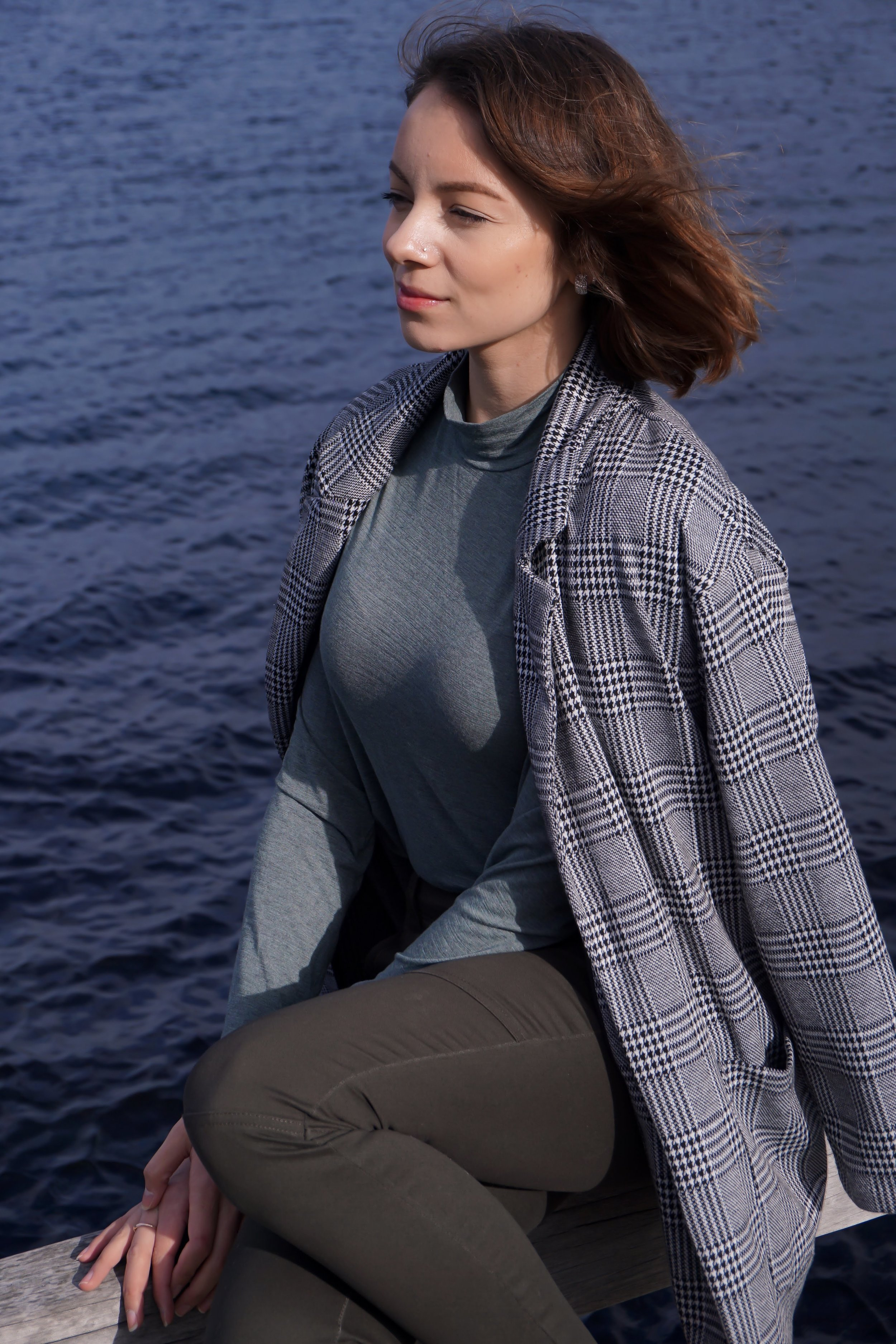 A blogger posing near the water, wearing camel green ankle pants, turtleneck, black point heels, and a houndtooth blazer.