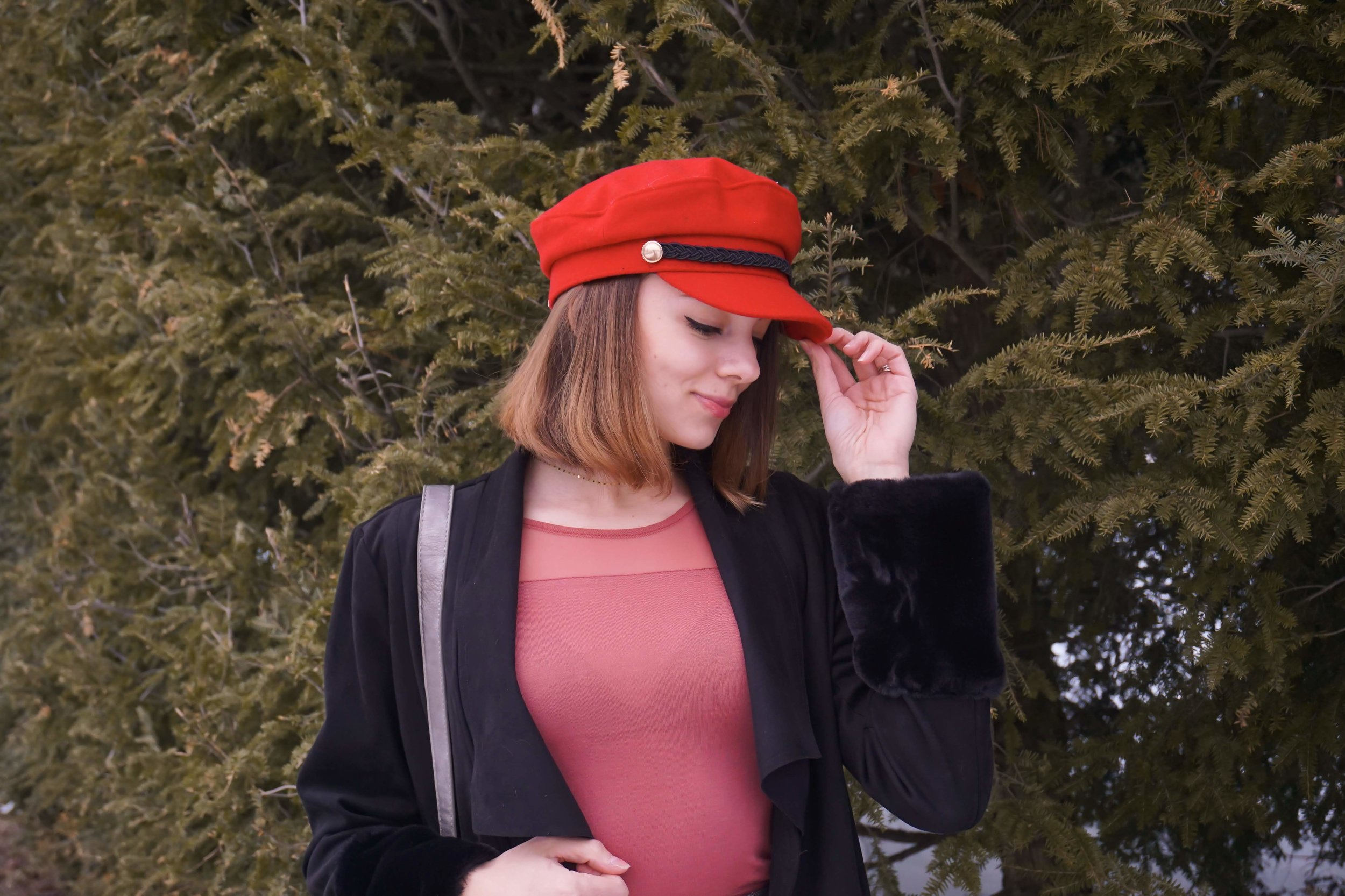 Fashion blogger is posing in the nature, wearing a red hat, salmon top, black jacket, gray pencil skirt, and faux-leather boots.
