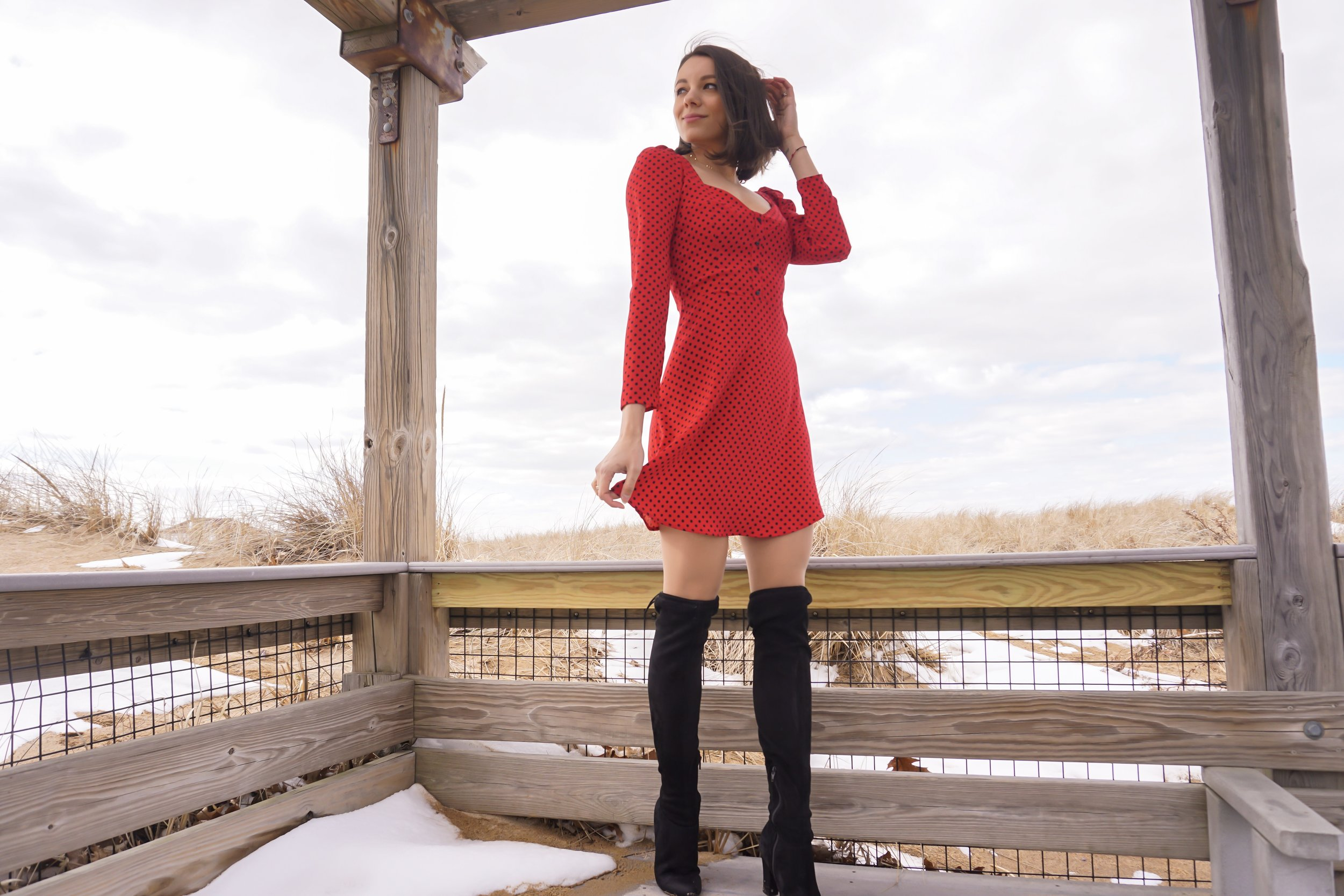 A fashion blogger posing near the ocean, wearing a red Zara dress, and black over the knee boots.