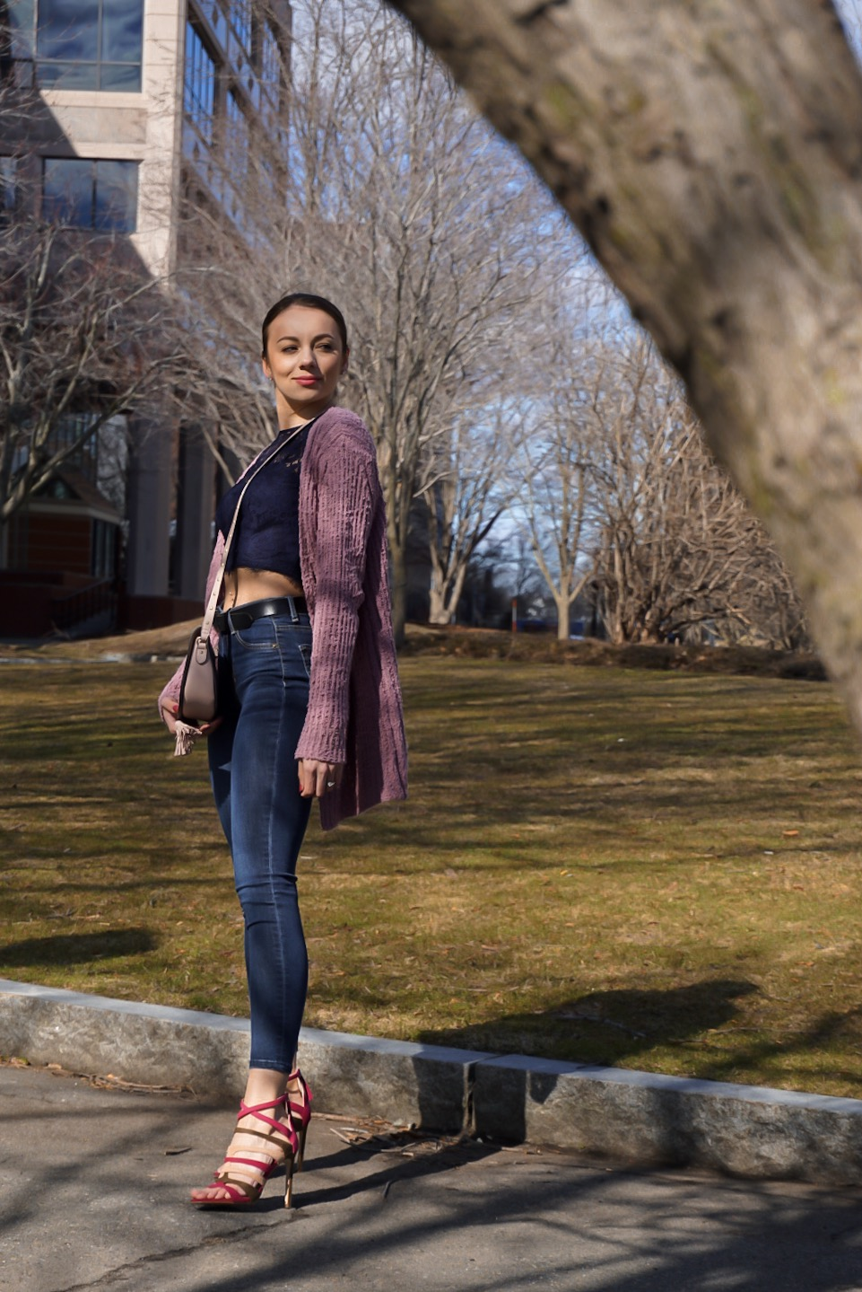 A fashion blogger wearing a lace blue crop top, long pink sweater, dark blue jeans, Zara pink heels, and pink Victoria Secret crossover bag.