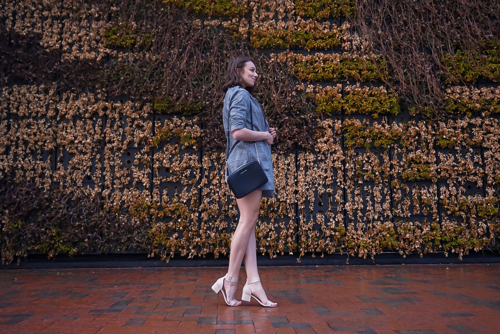 Spring outfit inspiration on a fashion blogger: houndstooth blazer, dark pink shirt, black short shorts, nude pumps with open toes, and a Michael Kors crossover bag.
