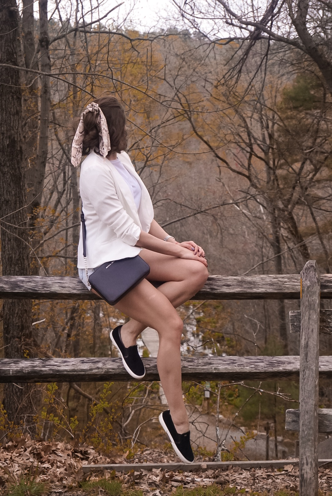 A fashion blogger posing in a forest, wearing a white crop top, white blazer, light denim shorts, black Michael Kors bag, and black Michael Kors slip ons.