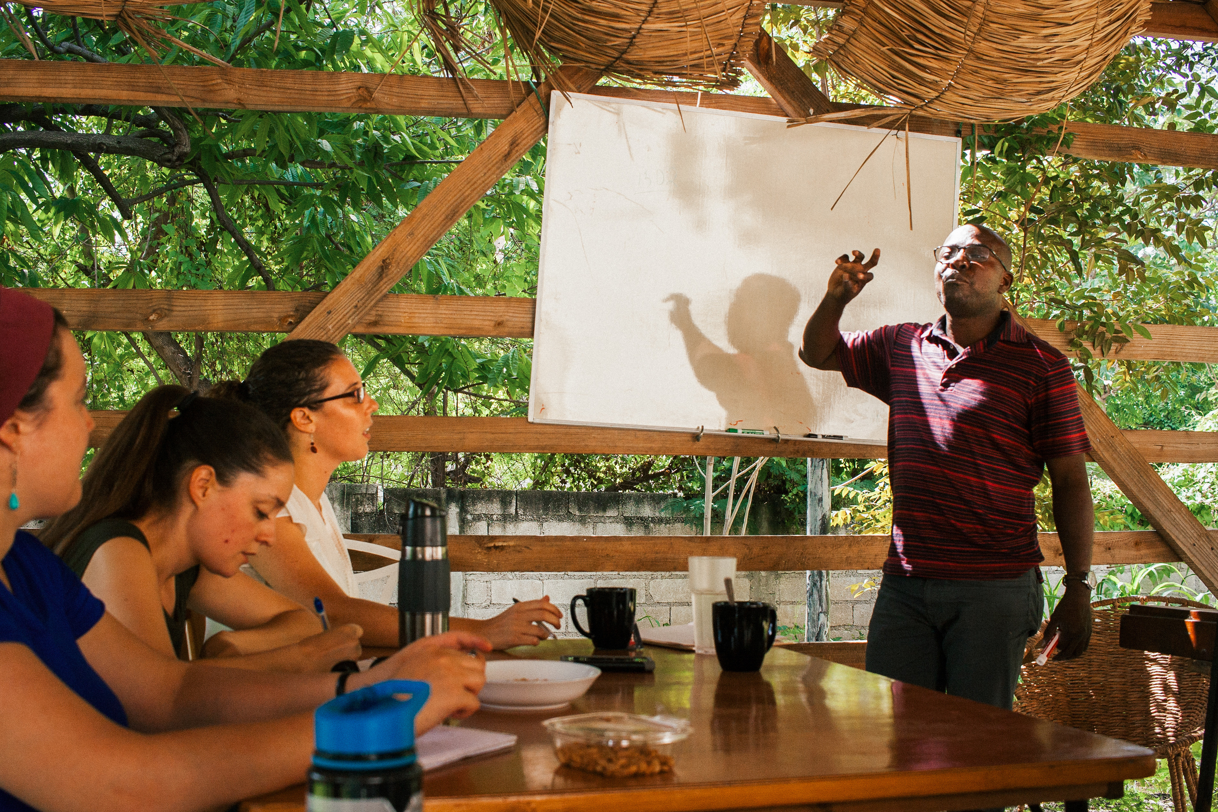 Nixon Boumba (right) teaches on Haitian history at the MCC Haiti office. Anna Vogt